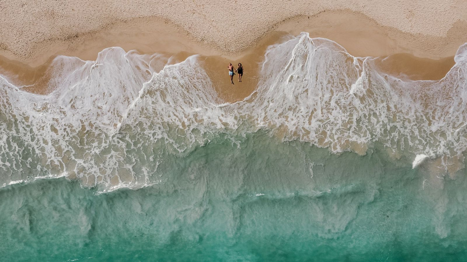 drone photo of couple on beach during engagement session