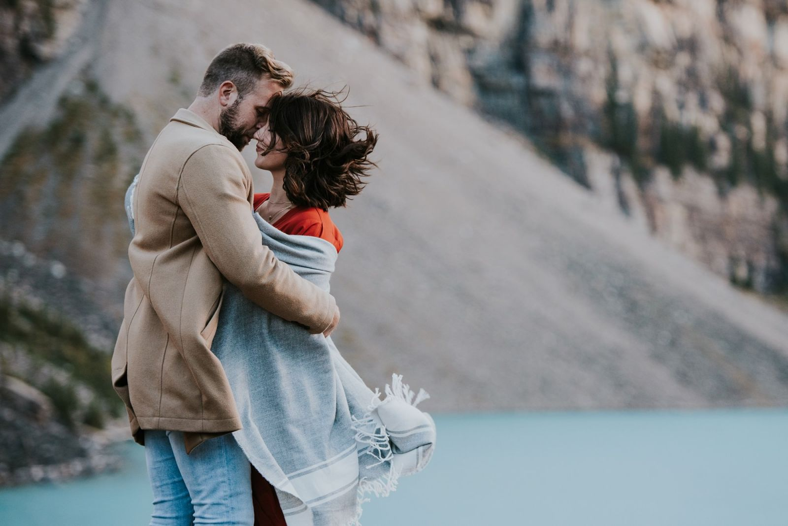 couple in the wind in mountains with blanket during engagement session