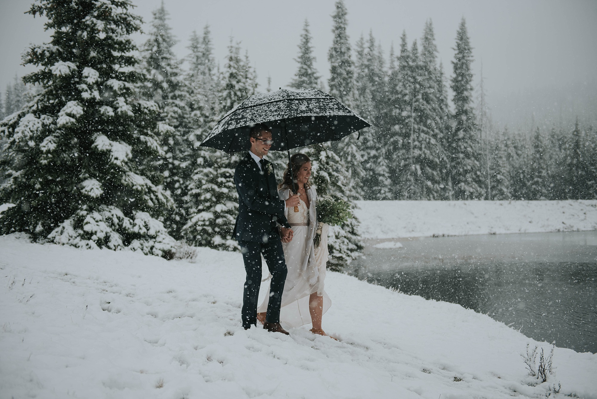 intimate wedding ceremony with bride and groom in the snow in winter mountain elopement