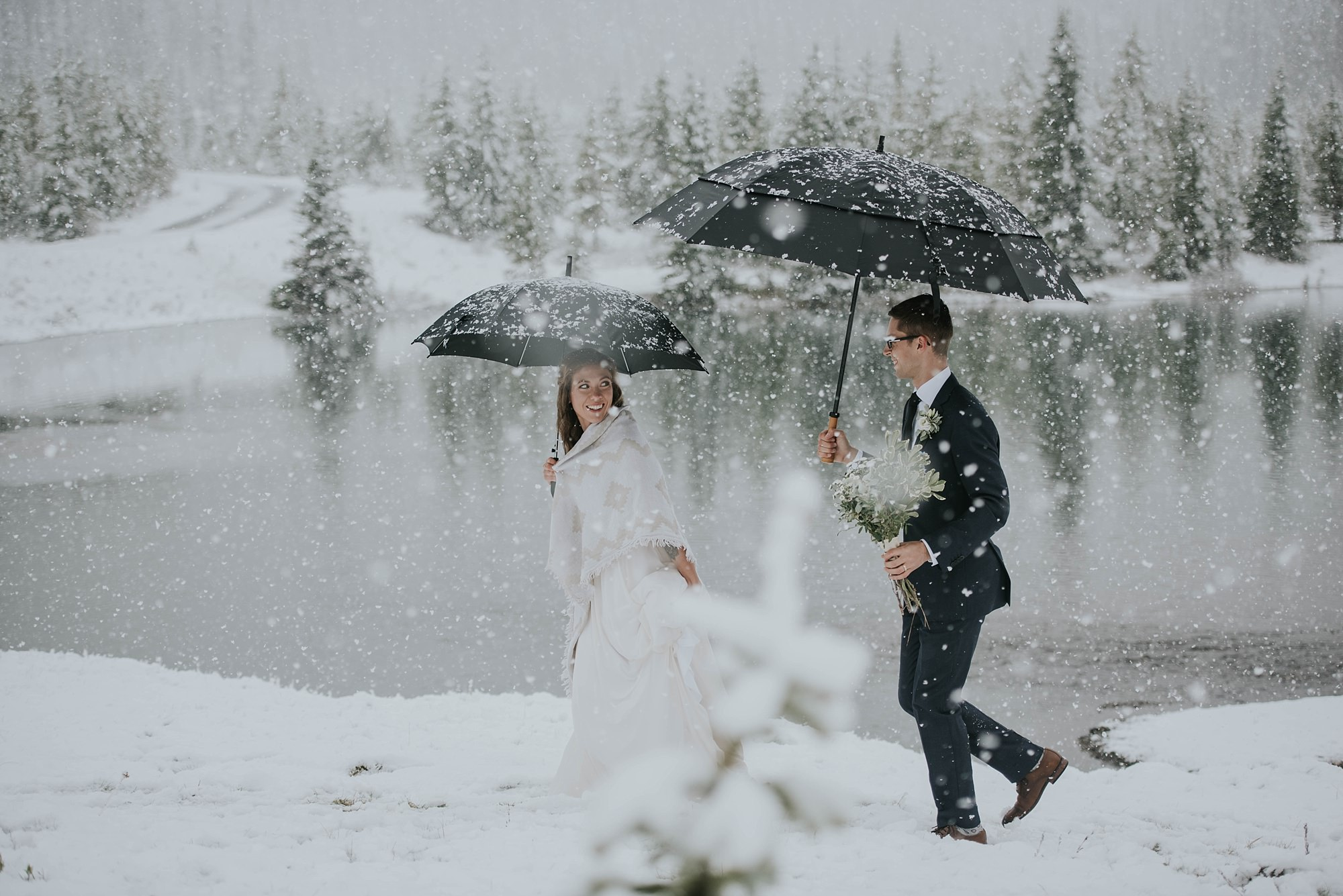 bride and groom walking in the snow in winter mountain elopement in kananaskis