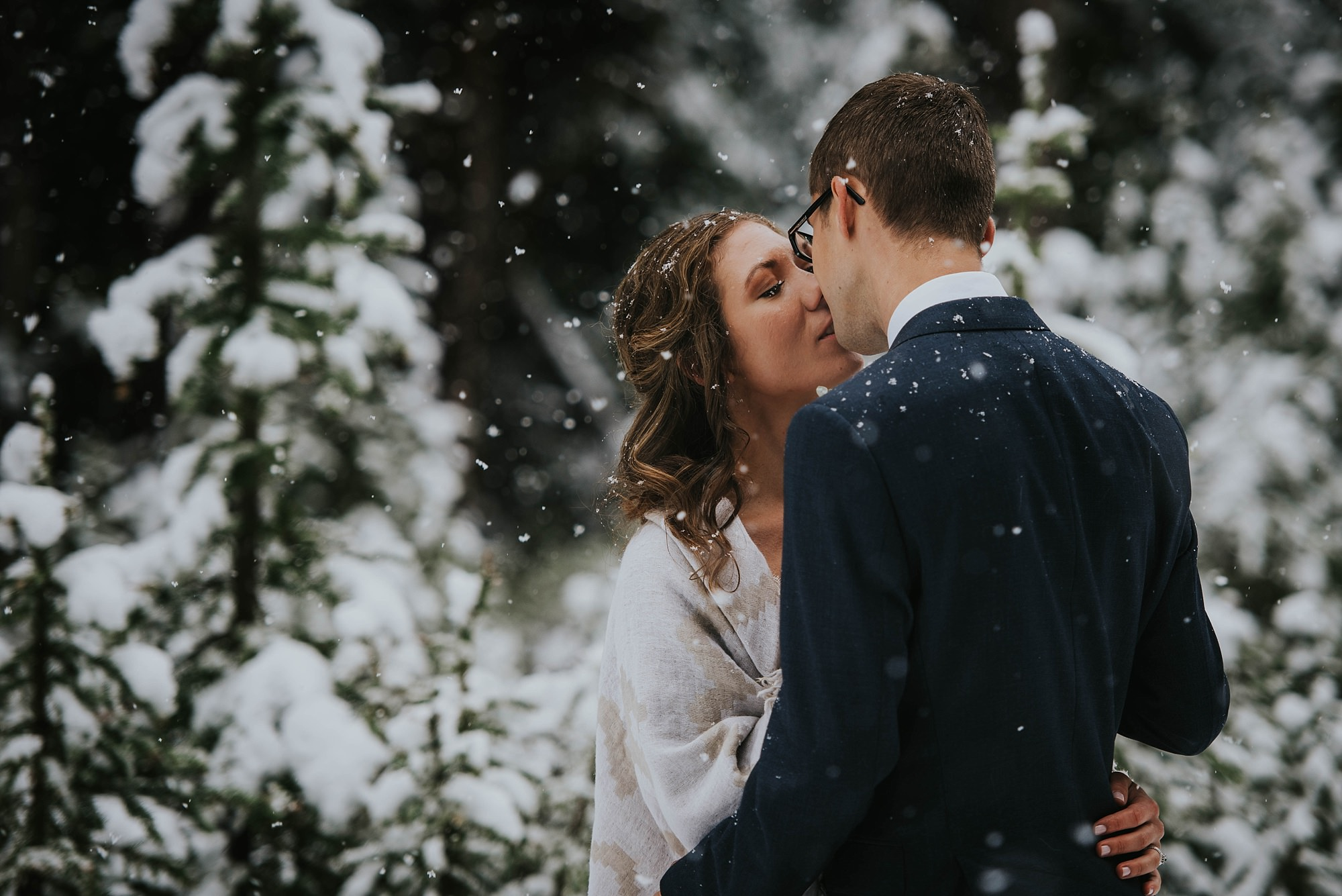 bride and groom kissing in the snow during Kananaskis winter wedding