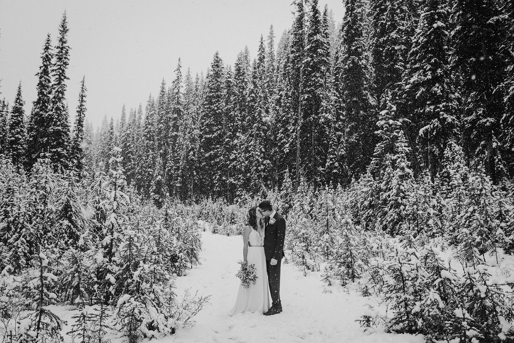 bride and groom embracing in the snow during Kananaskis winter elopement