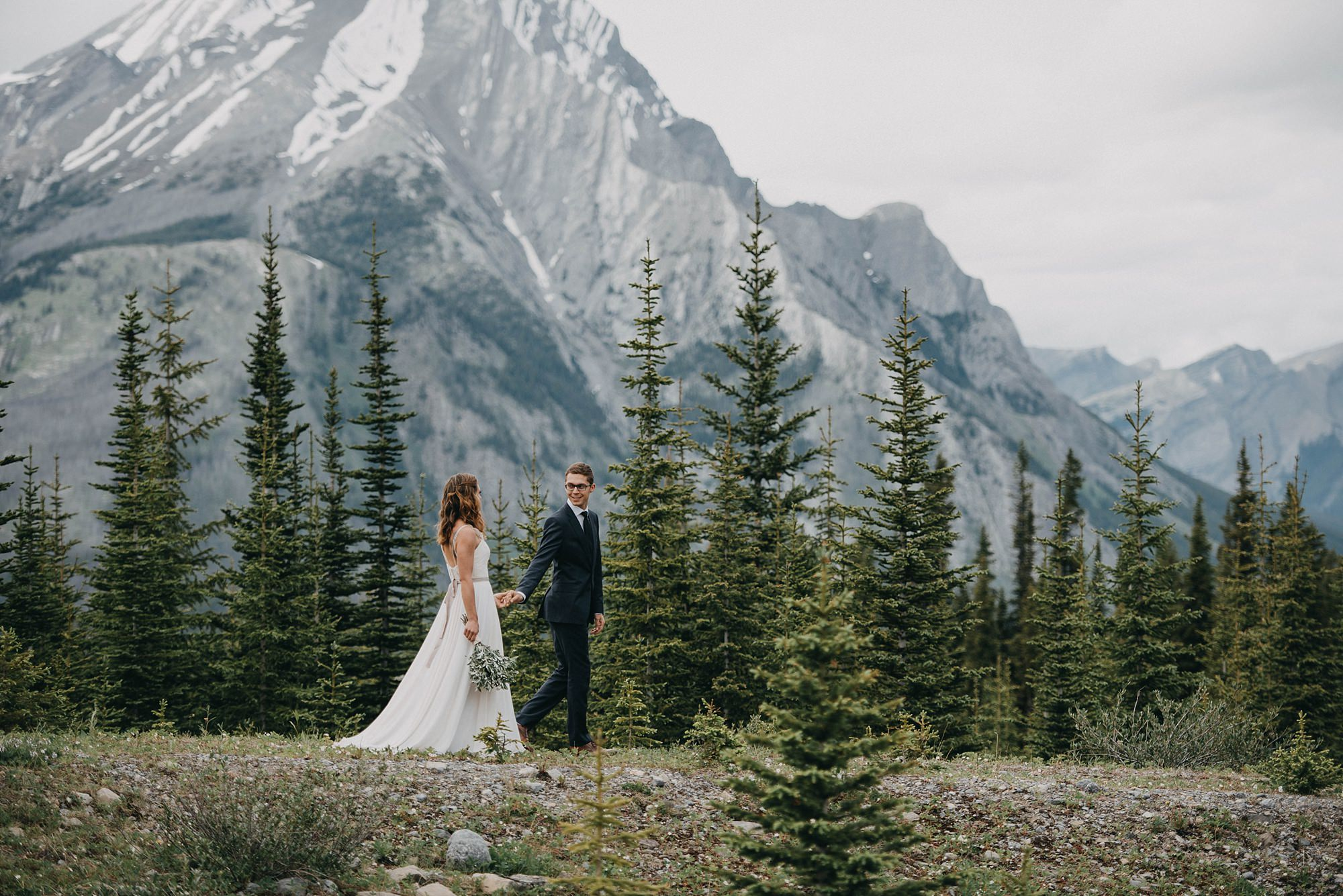 bride and groom standing together in field on deck with Kananaskis mountains behind them during Kananaskis wedding