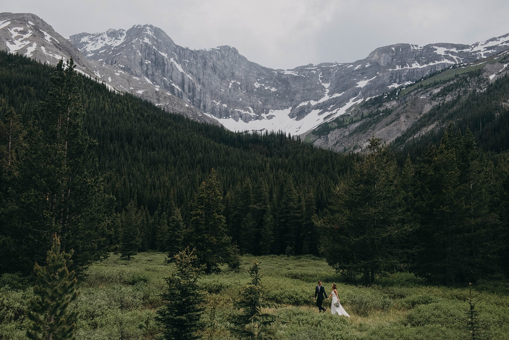 boho bride and groom walking in candid bridal portraits in Kananaskis wedding