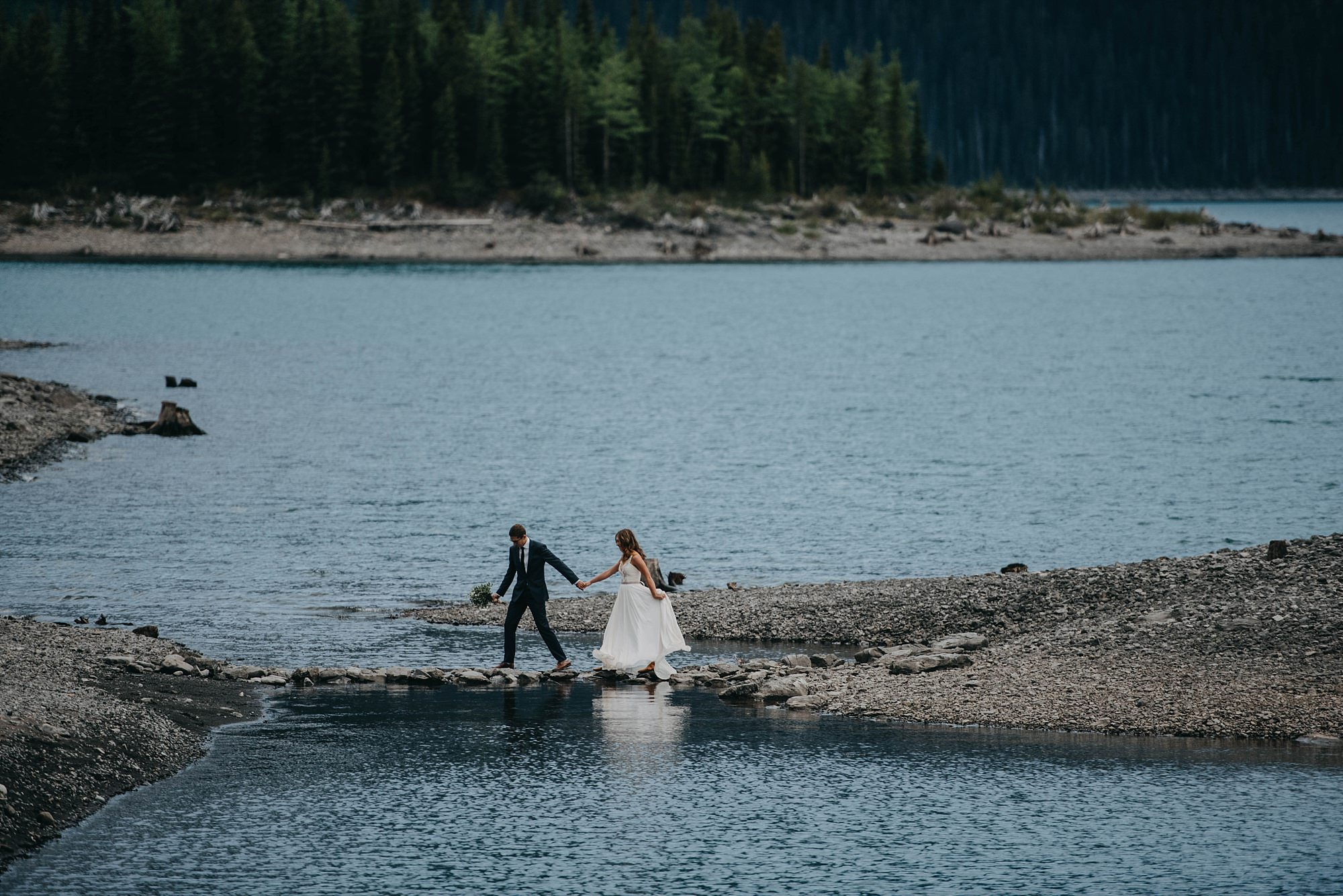 bride and groom walking along natural bride at Kananaskis lakes during bridal portraits in mountain elopement