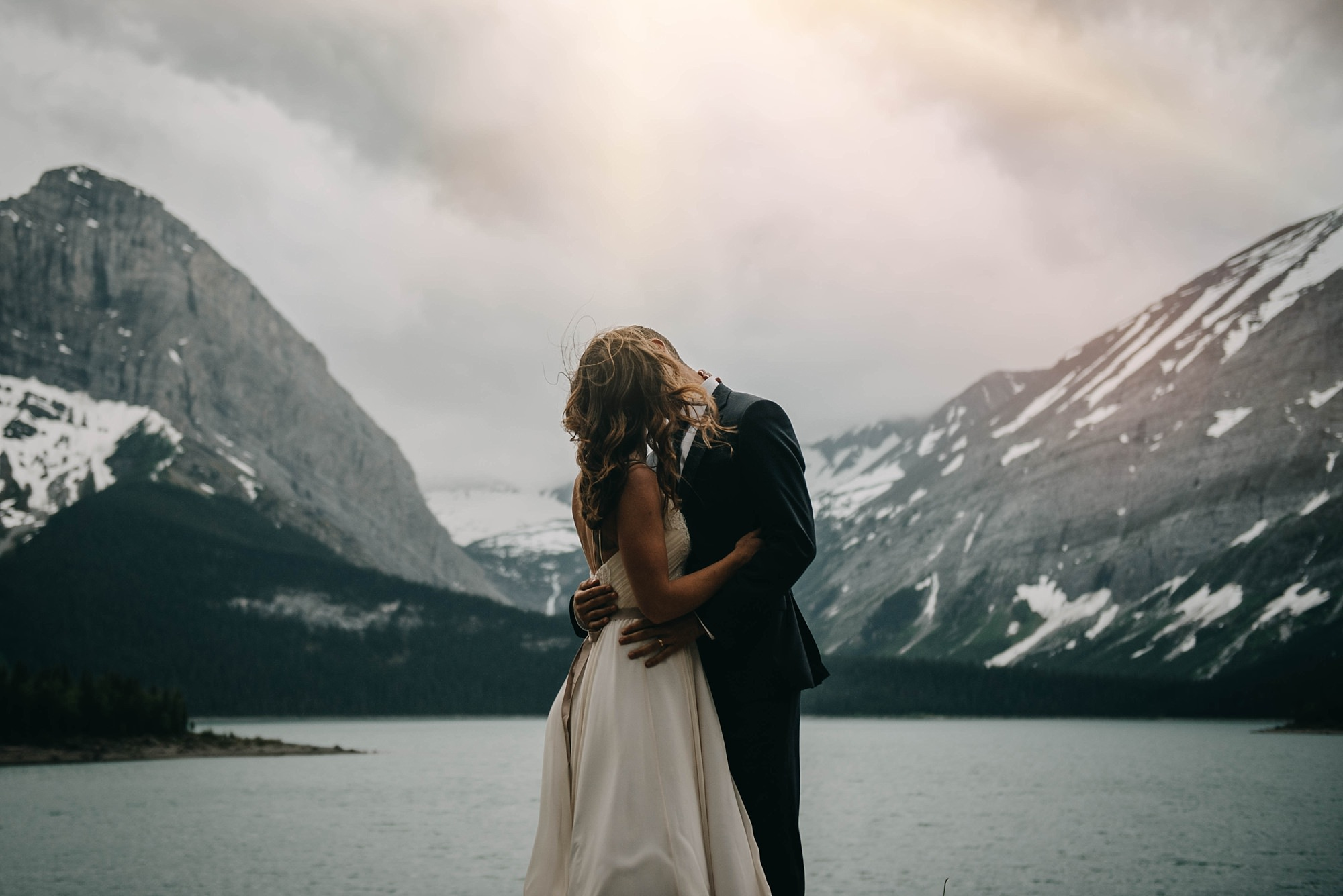 bride and groom embracing at lake in the mountains during bridal portraits in boho Kananaskis wedding