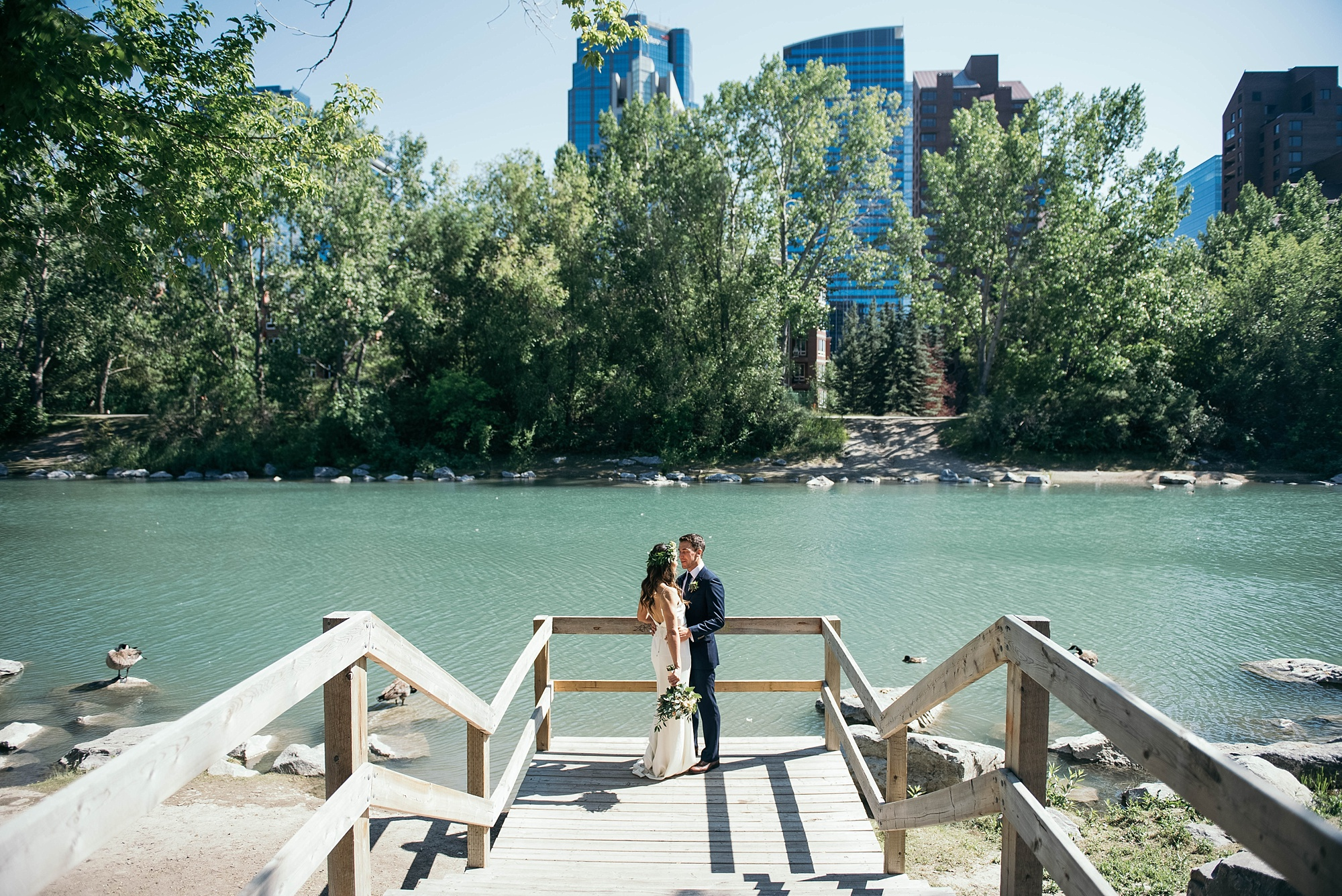 bride and groom standing together on a bridge in princes island park with downtown calgary behind the river