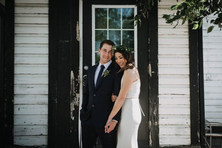 simple and elegant styled bride and groom standing in front of black and white rustic buildling in calgary bonterra wedding