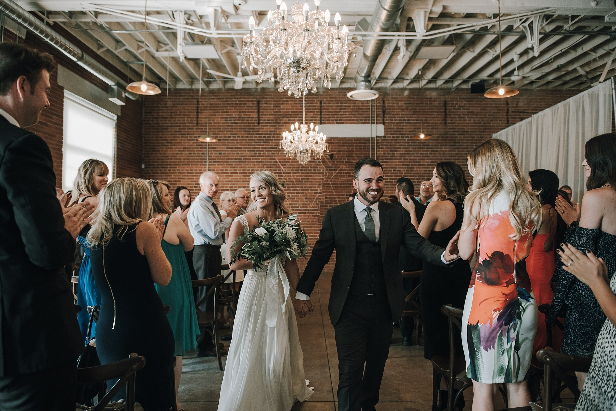 bride and groom exit ceremony during modern warehouse wedding in calgary