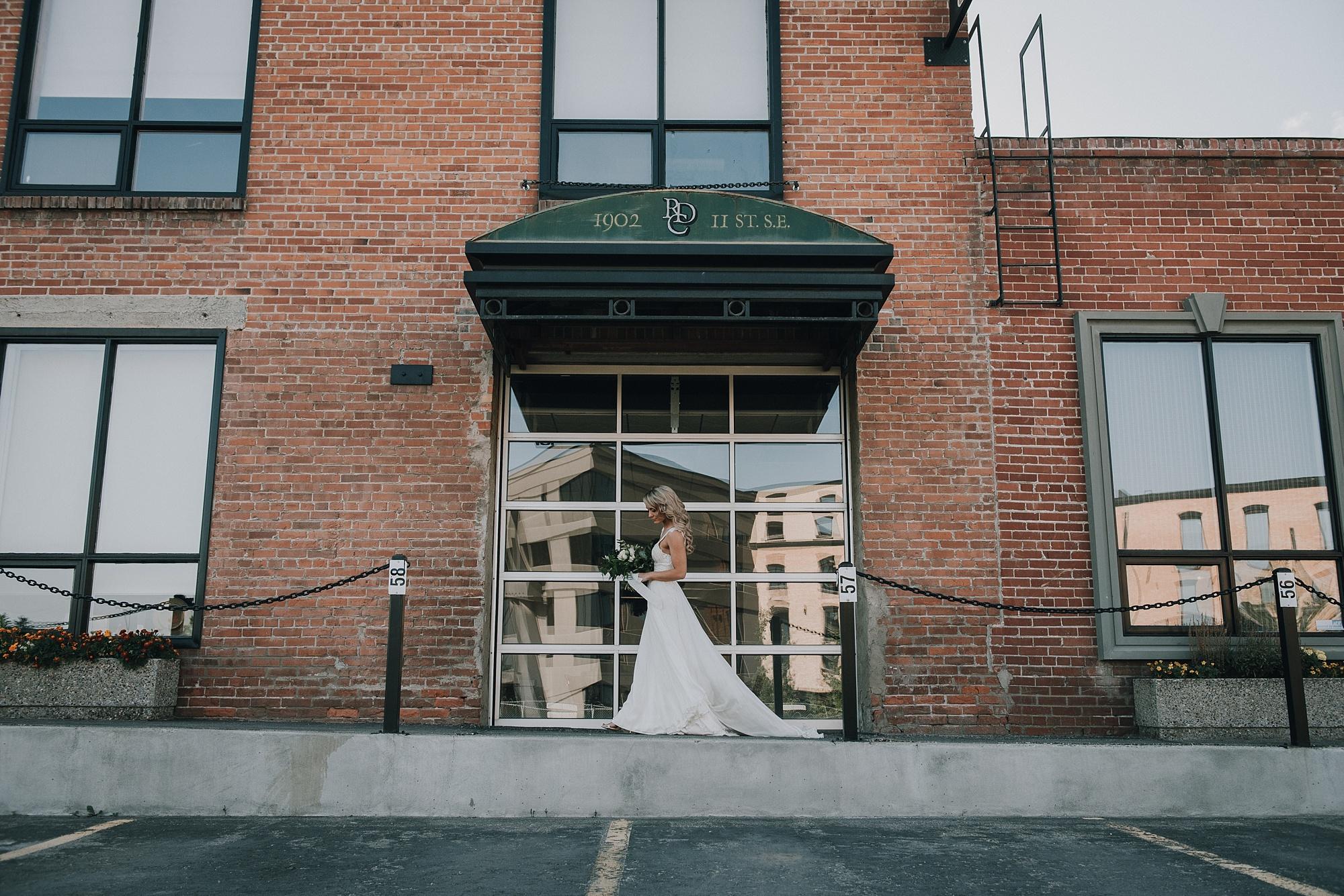 bride walking in front of art deco wedding reception venue in calgary