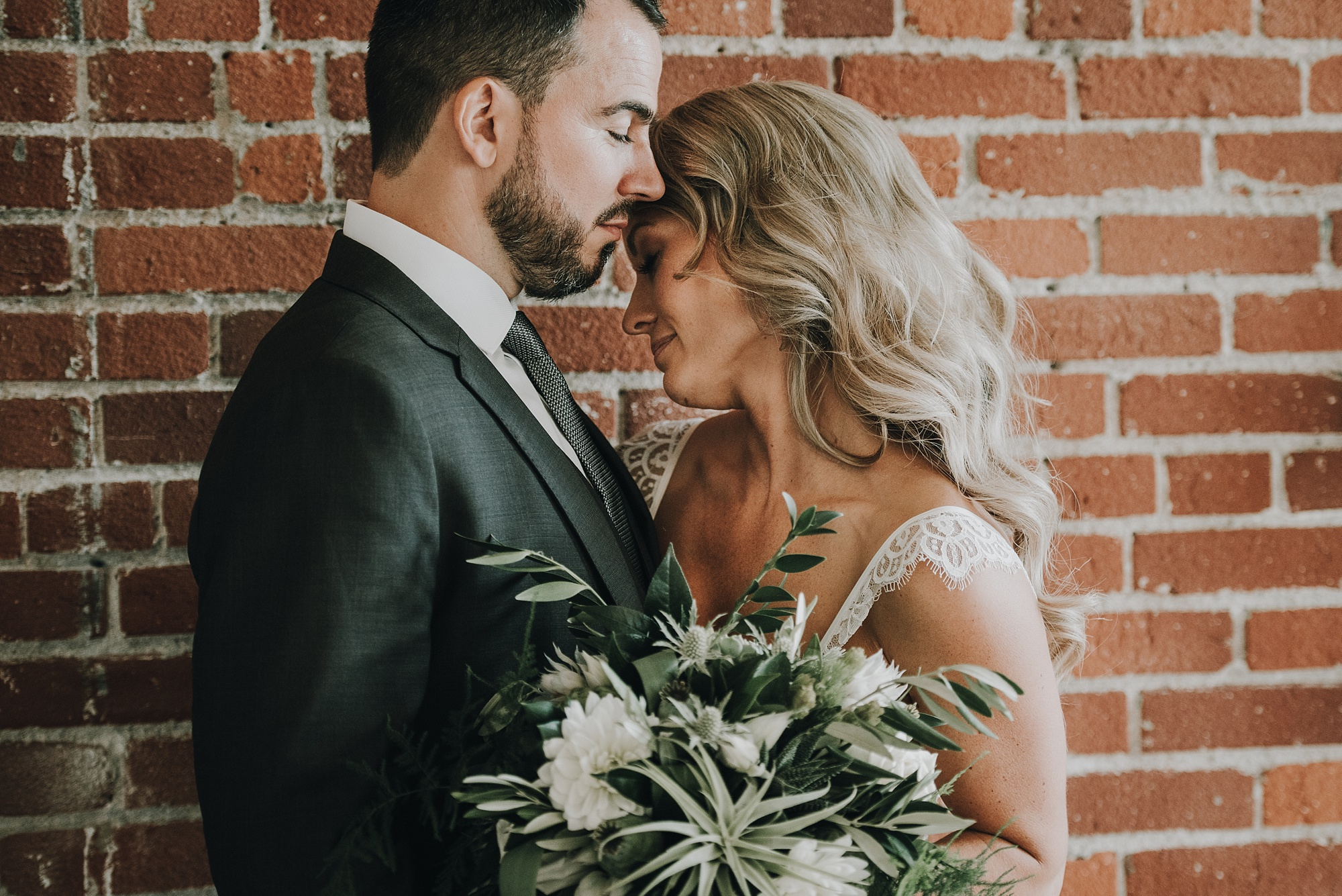 Bride and groom in front of rustic brick wall in modern, industrial calgary wedding