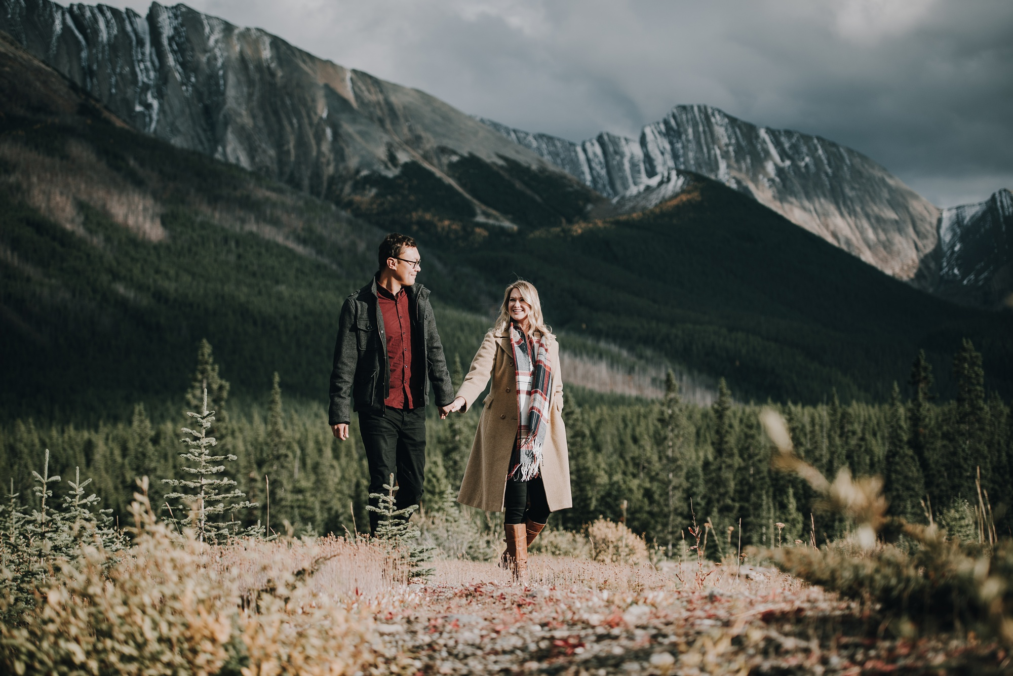 couple walking through a field in Kananaskis engagement session