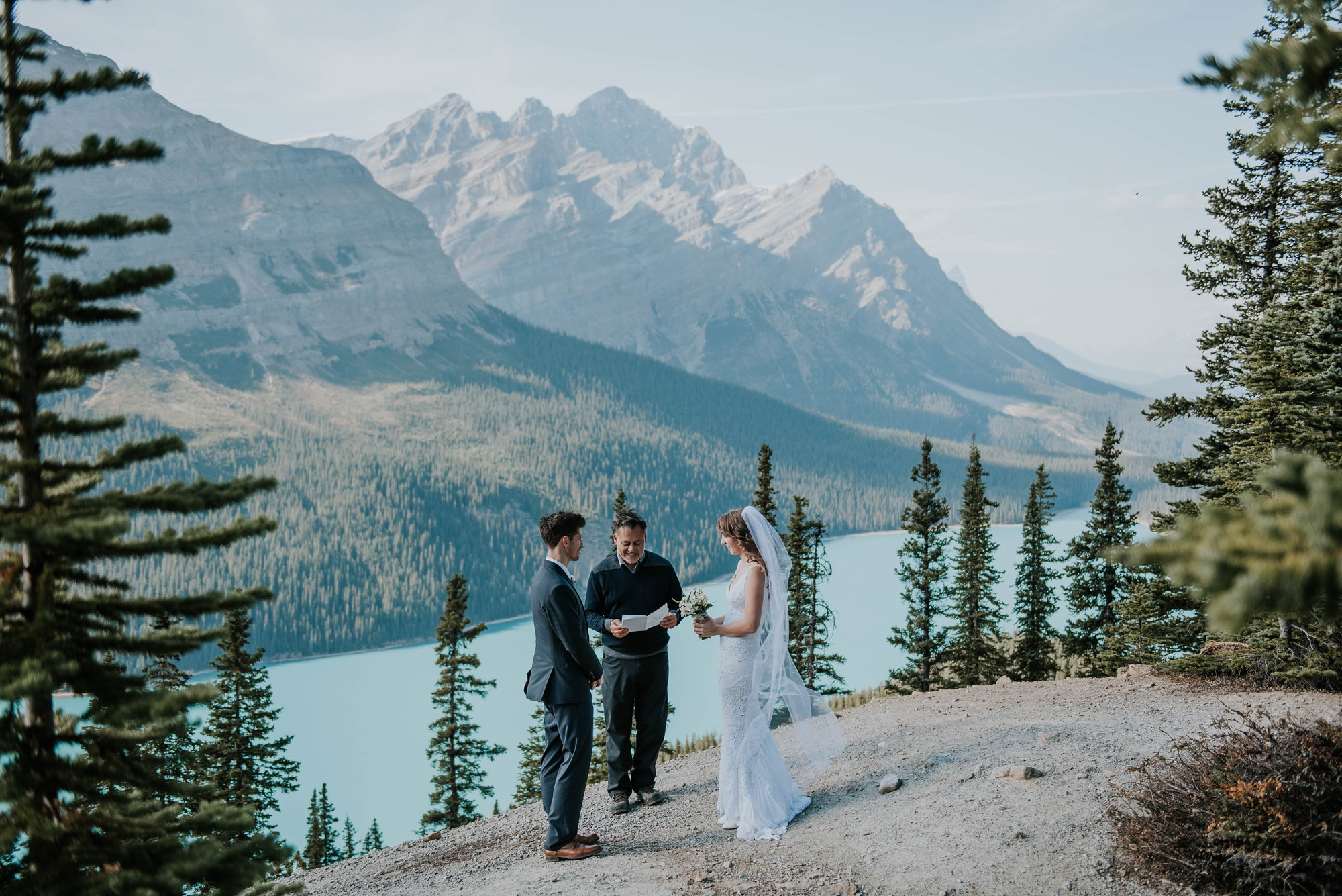 bride and groom with celebrant in front of Peyto Lake for wedding ceremony