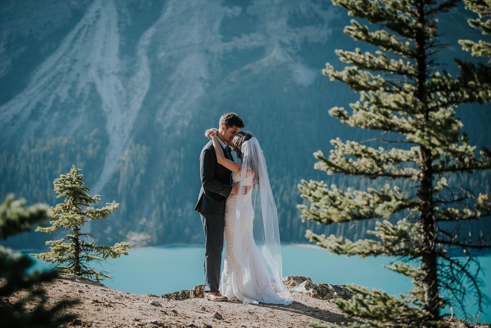 bride and groom embrace and kiss during bridal portraits at Peyto Lake