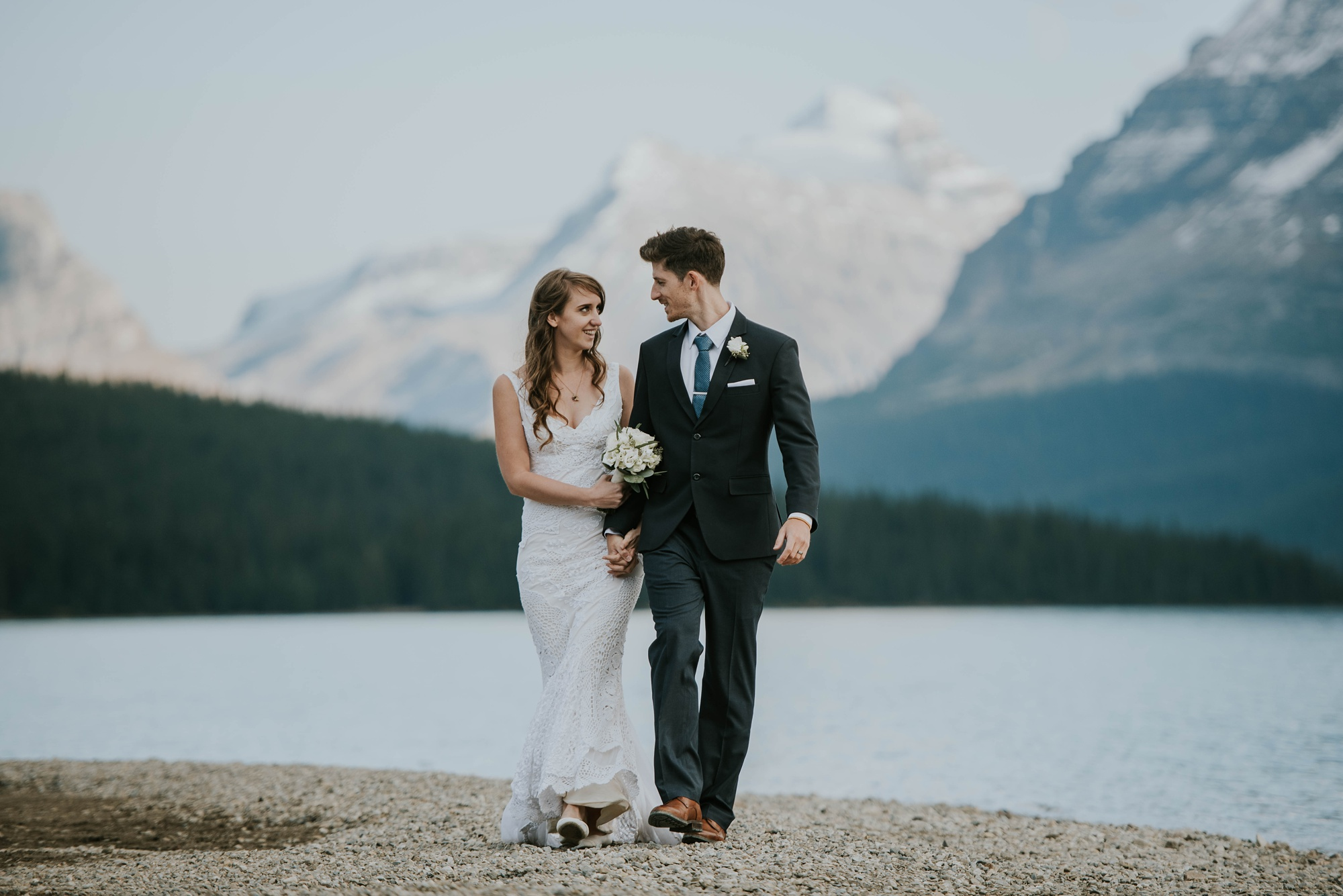 bride and groom walk along the shore of bow lake in the Canadian rockies mountains