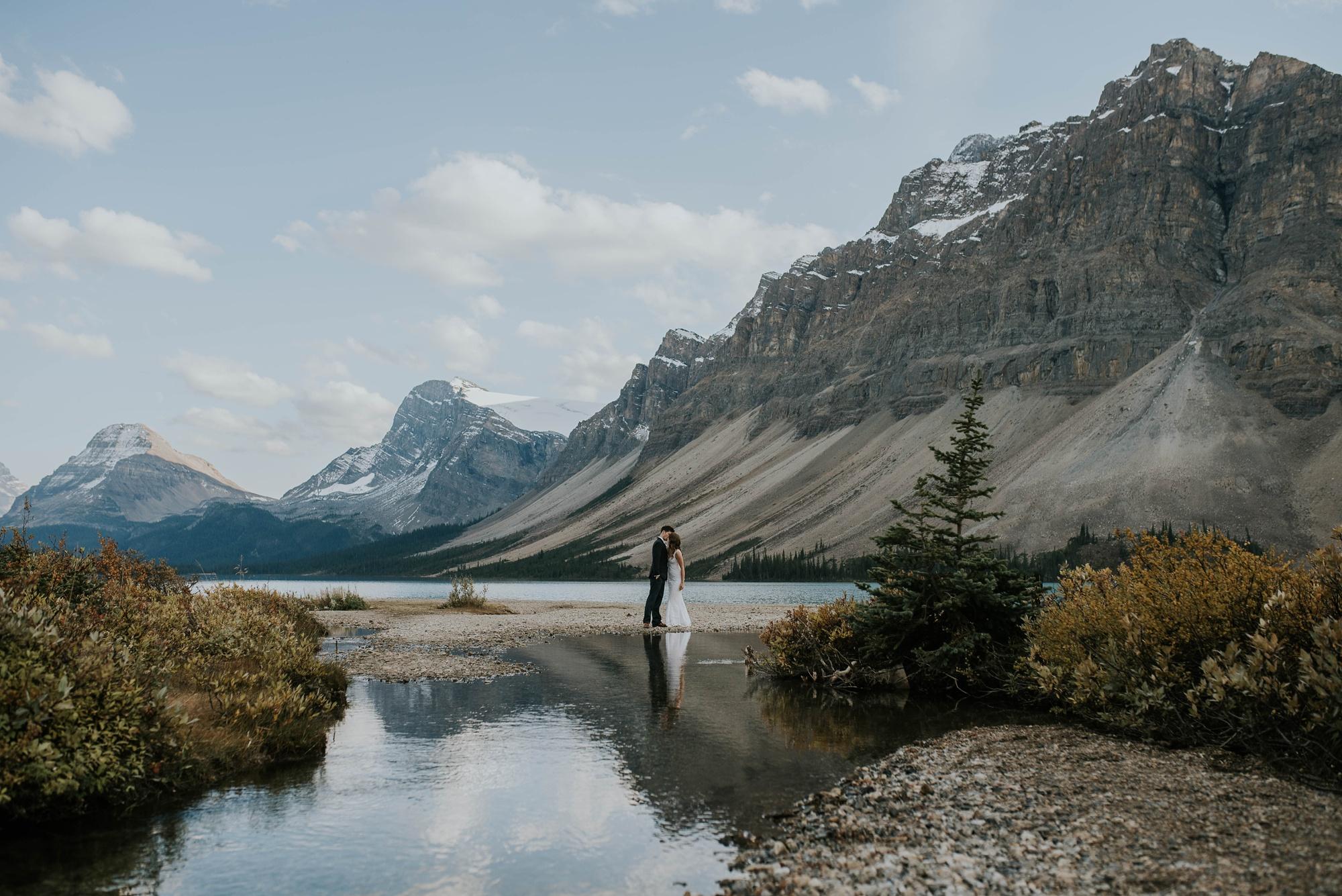 bride and groom walk along bow lake during intimate Peyto Lake elopement