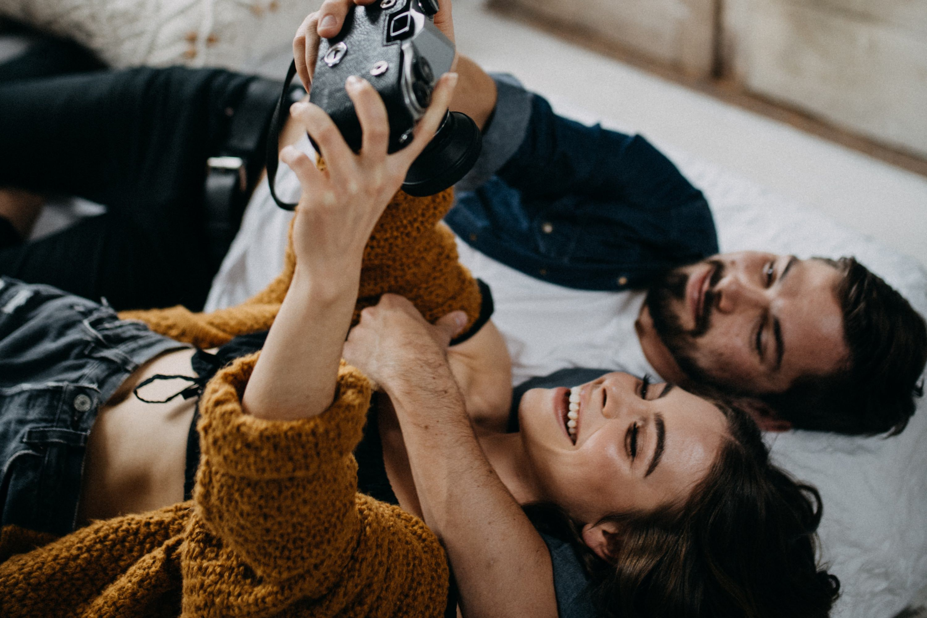boho engaged couple taking pictures of each other on bed during in home engagement session