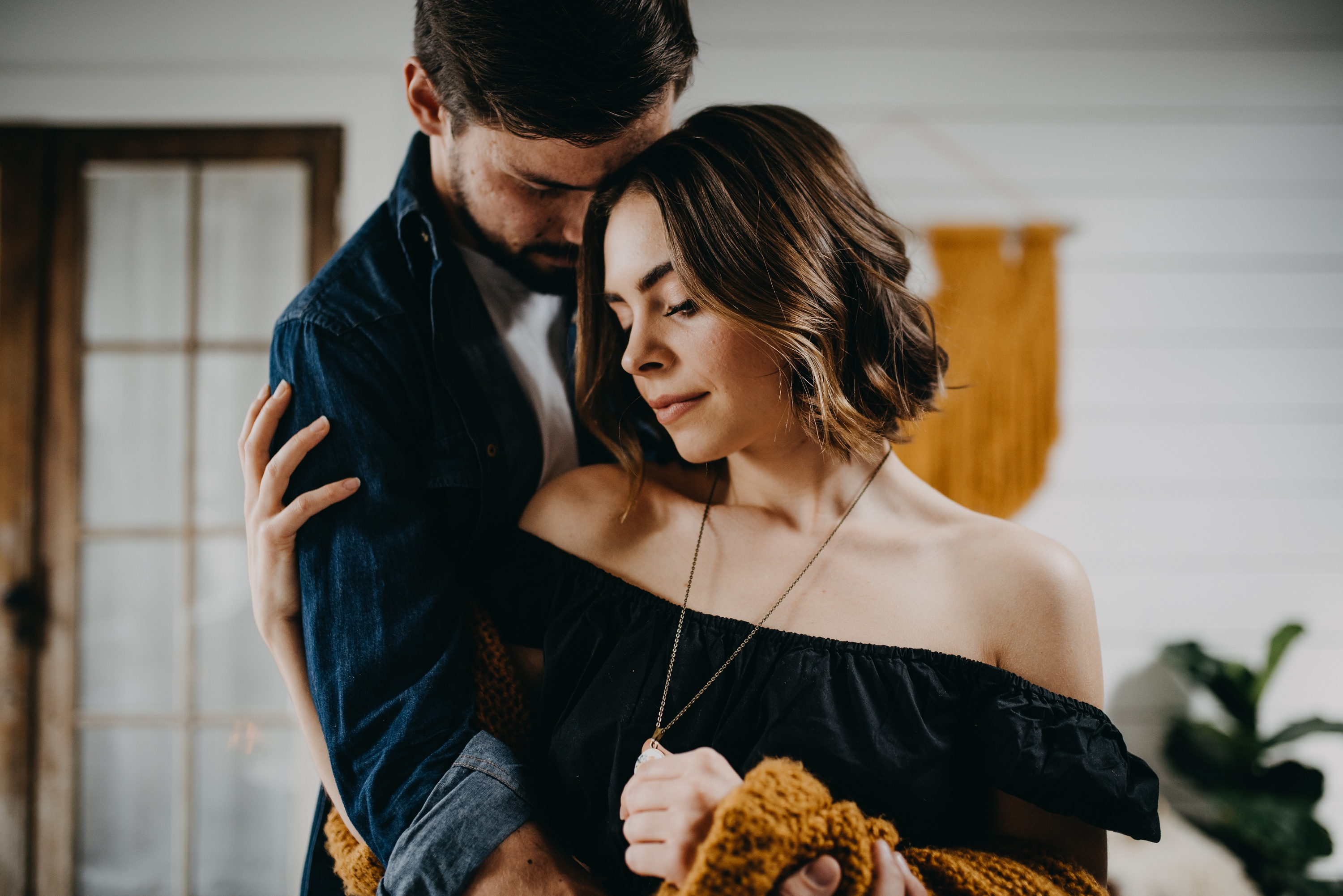 boho Engaged couple in living room during in home engagement session
