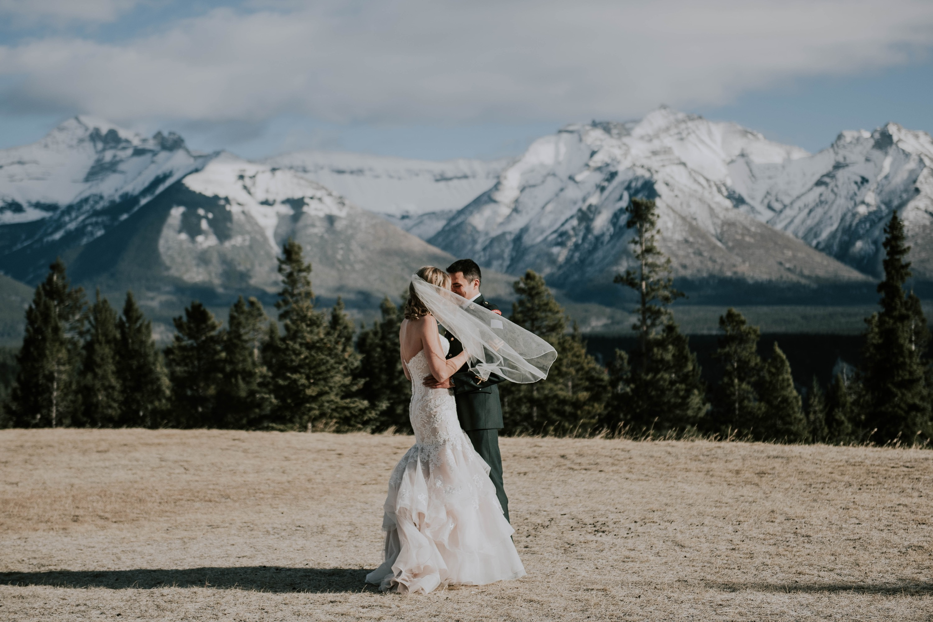 bride and groom kissing in the Banff mountains in winter wedding