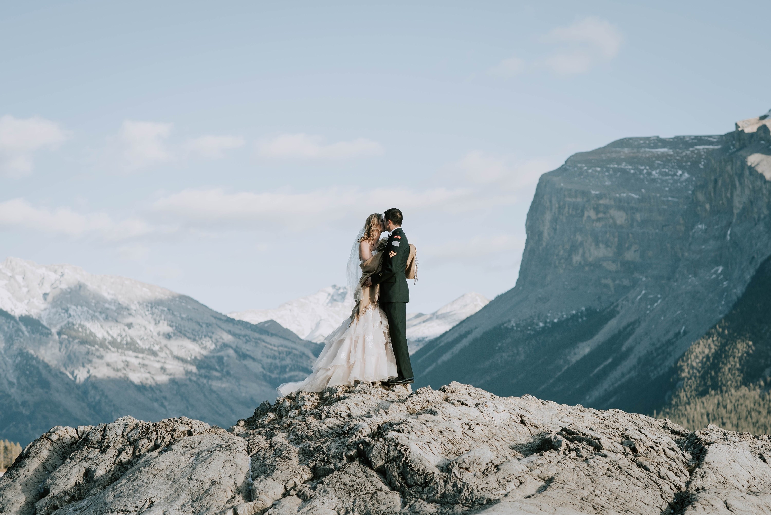bride and groom standing on a rock in the Banff mountains during winter wedding