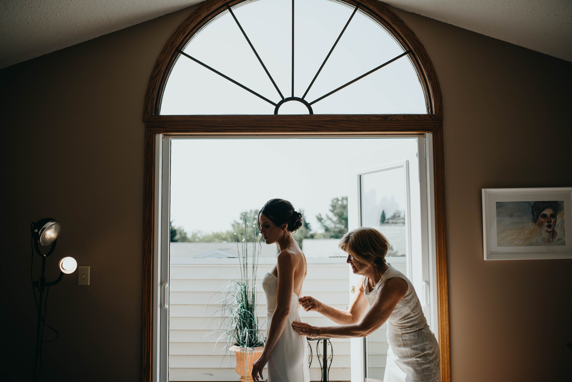 bride getting ready while mother zips up her classic and modern wedding dress