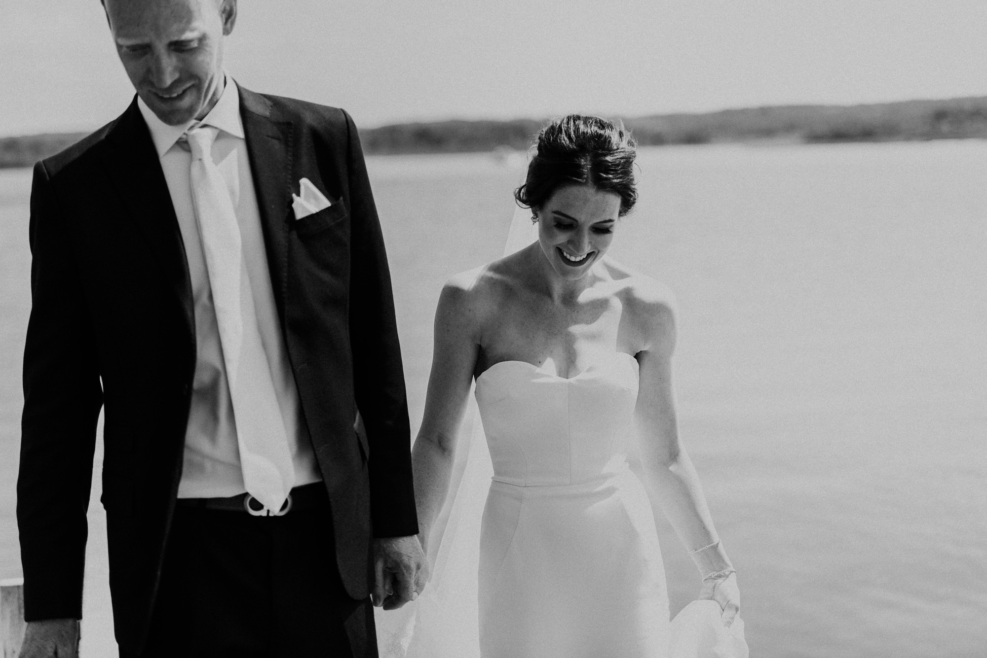 bride and groom walking on pier in bridal portraits at a lake in farm wedding