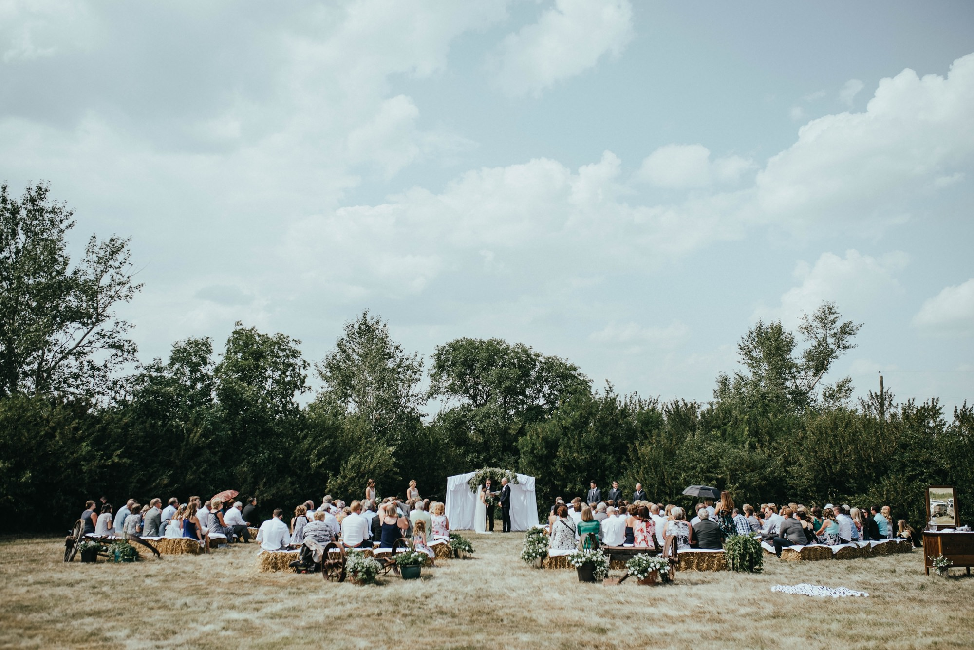 farm wedding ceremony with bride and groom and guests sitting on hay bails