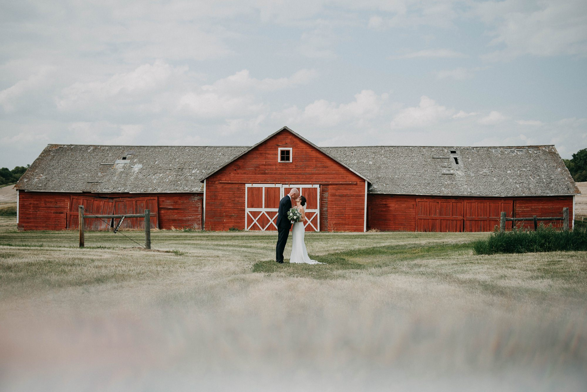 bride and groom in bridal portraits standing in front of a red barn hugging during farm wedding