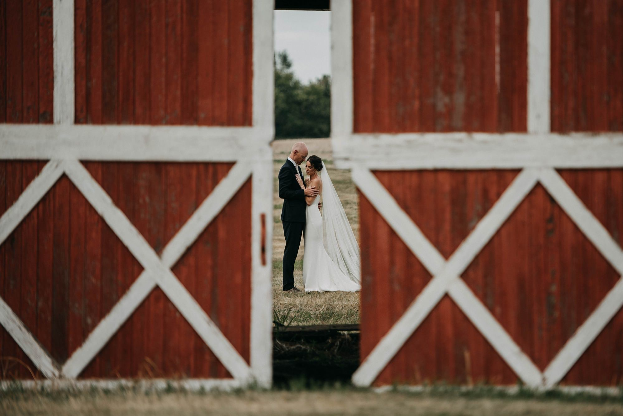 bride and groom in bridal portraits standing in front of a red barn hugging during farm wedding in provost