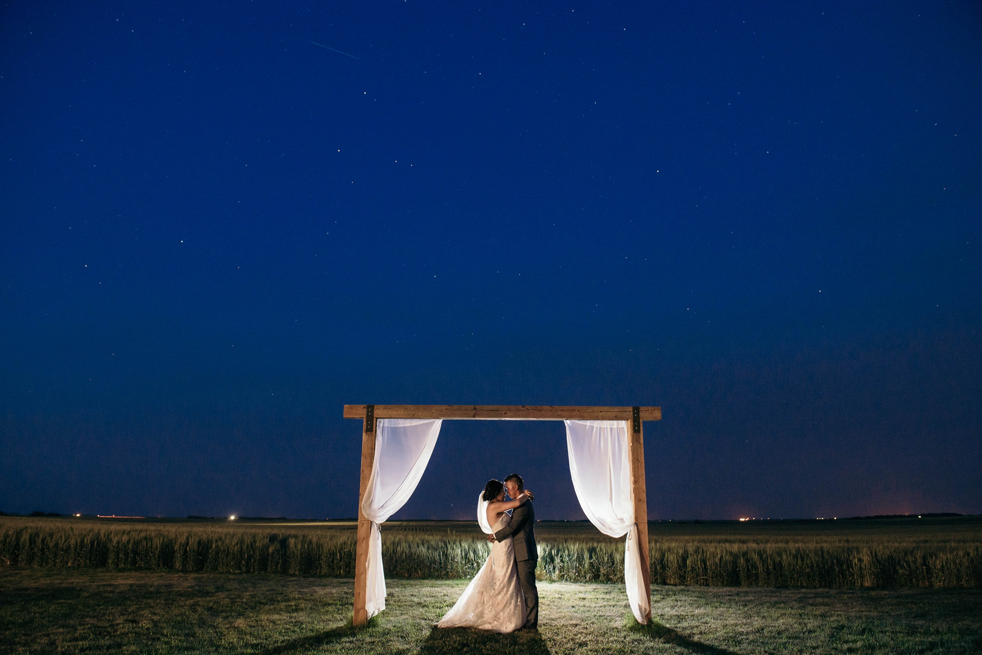 beautiful night shot of bride and groom in willow lane barn wedding in olds alberta