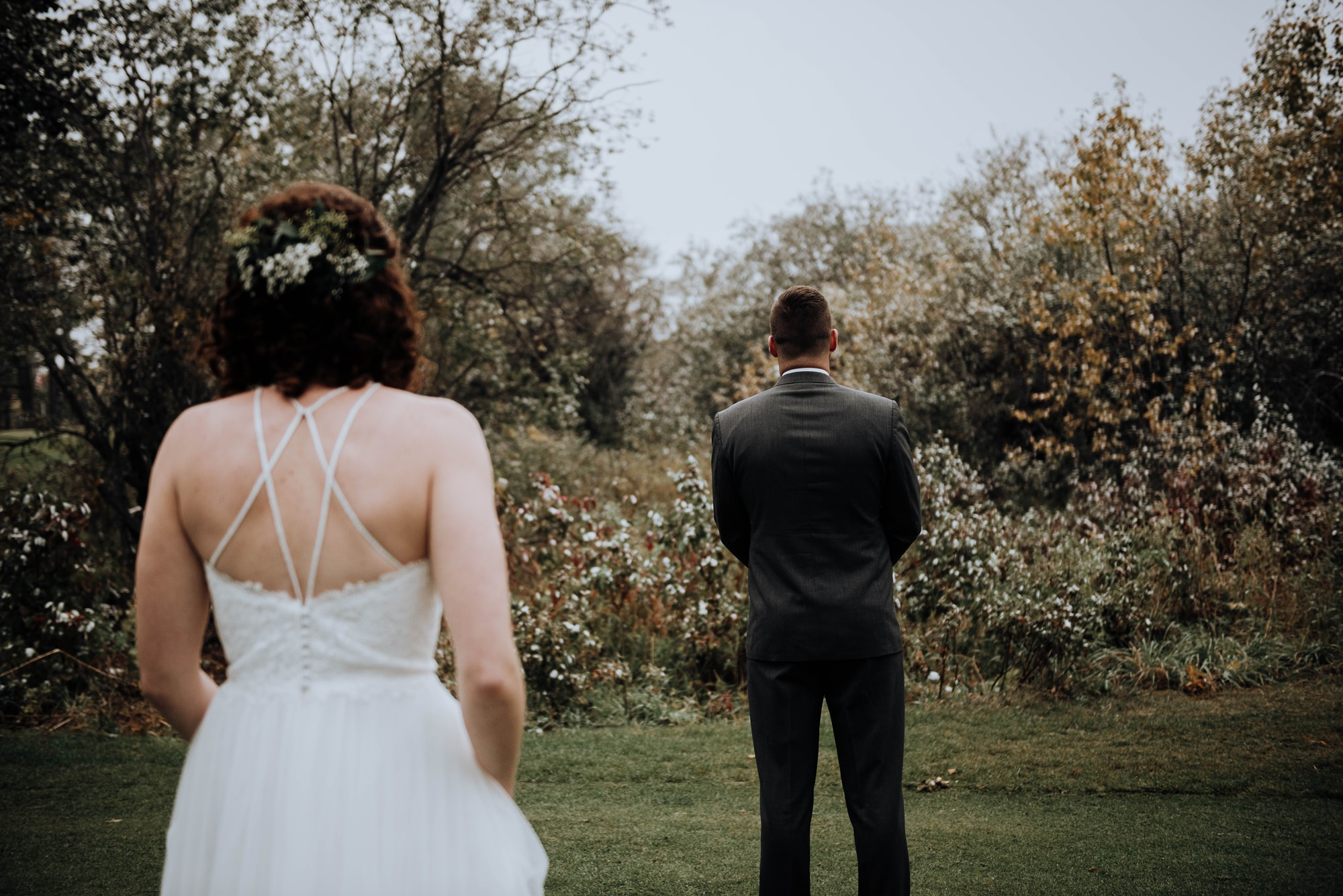 First look between bride and groom in the fall time at stylish modern and classic wedding at Calgary golf club river spirit golf and country club