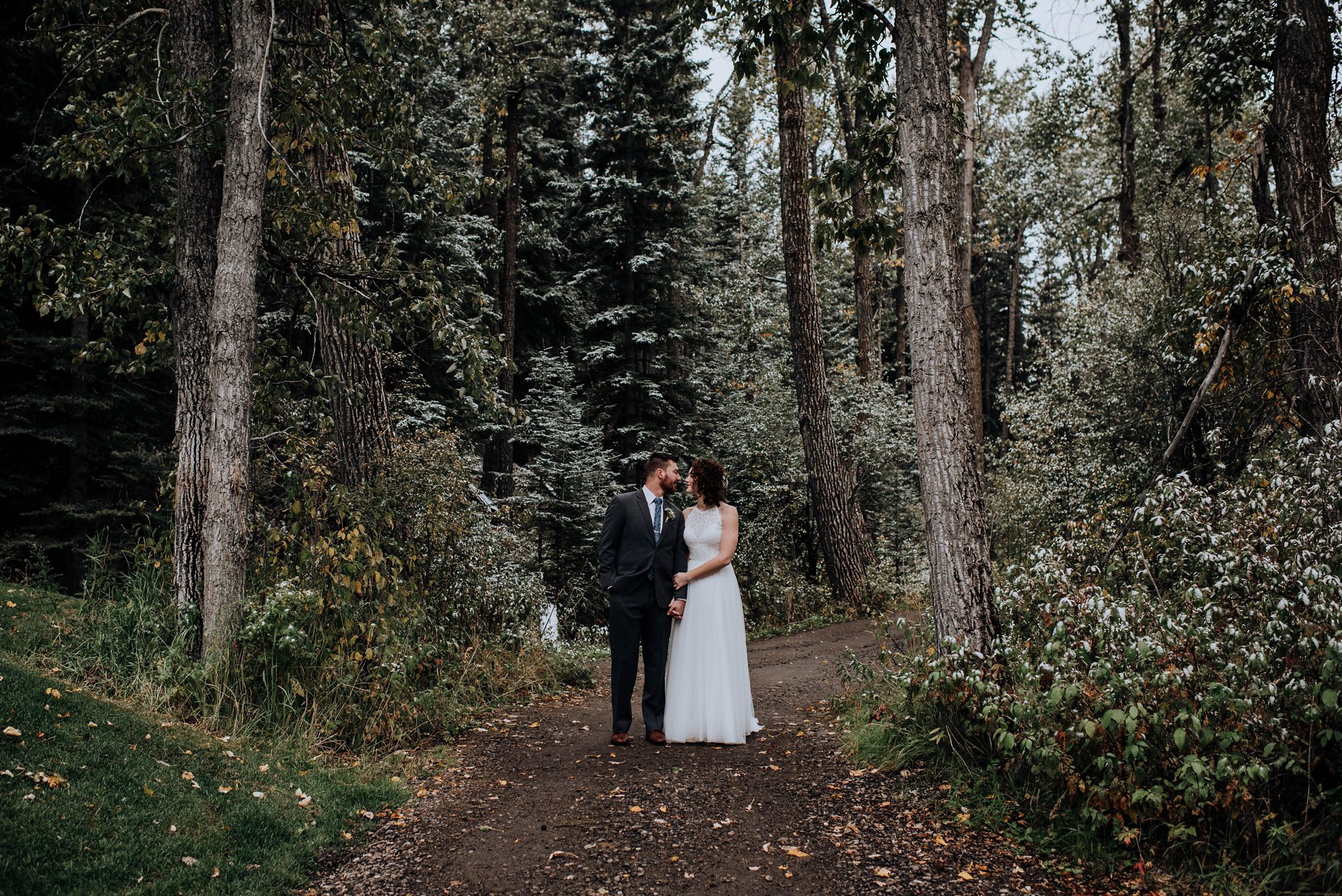 portraits of bride and groom in the forest in the fall time at stylish modern and classic wedding at Calgary golf club river spirit golf and country club