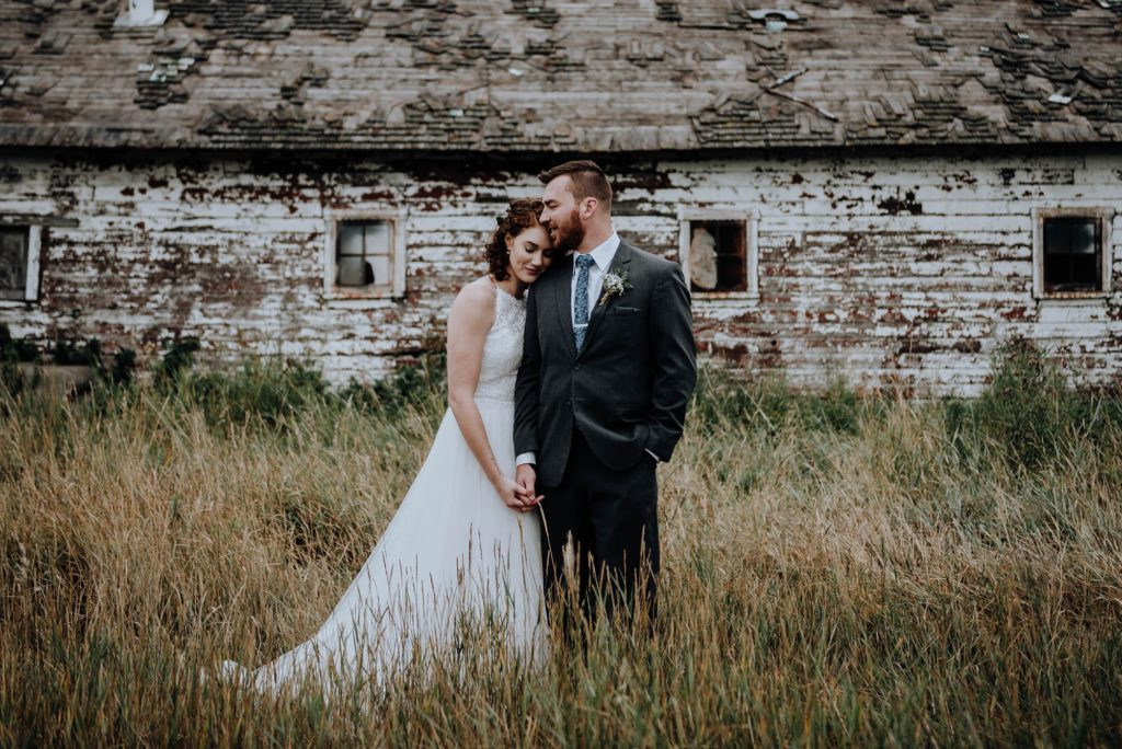 portraits of bride and groom in front of a white barn in the fall time at stylish modern and classic wedding at Calgary golf club river spirit golf and country club