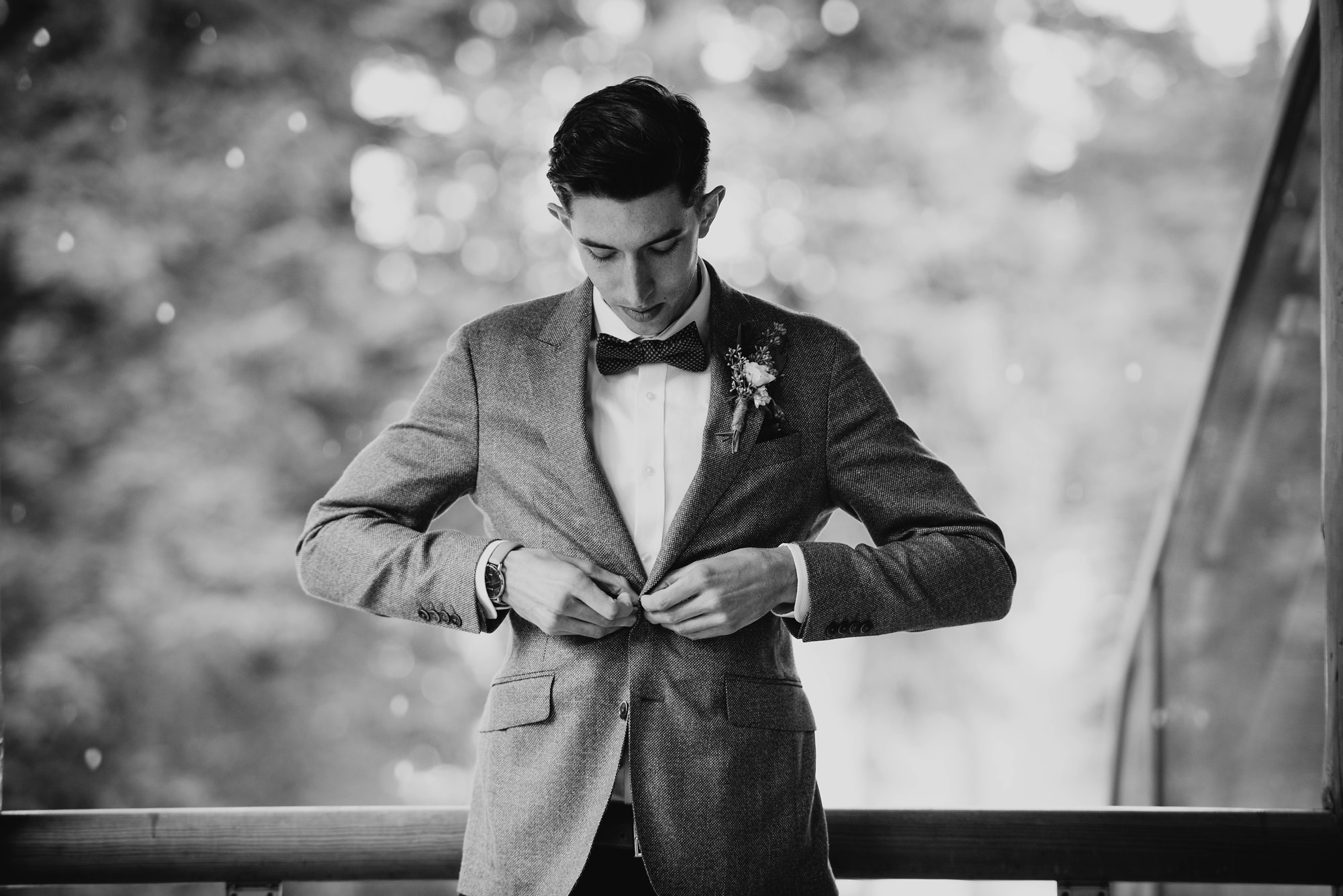 groom getting ready in moody mountain wedding captured at moraine lake lodge and Lake Louise in Banff Canada