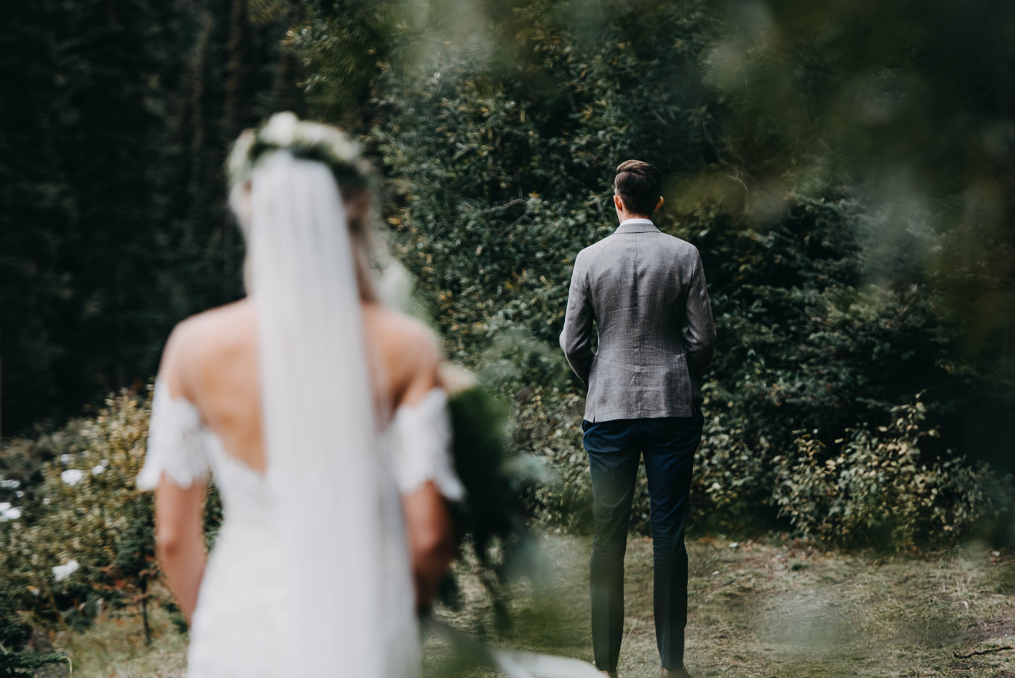 first look between boho couple in moody mountain wedding at lake louise in banff