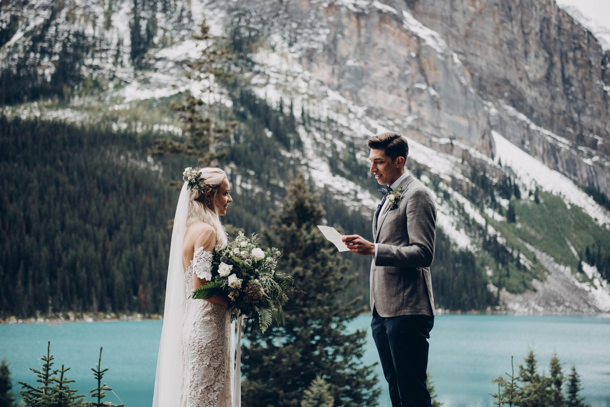 bride and groom exchange vows with mountains at lake louise elopement