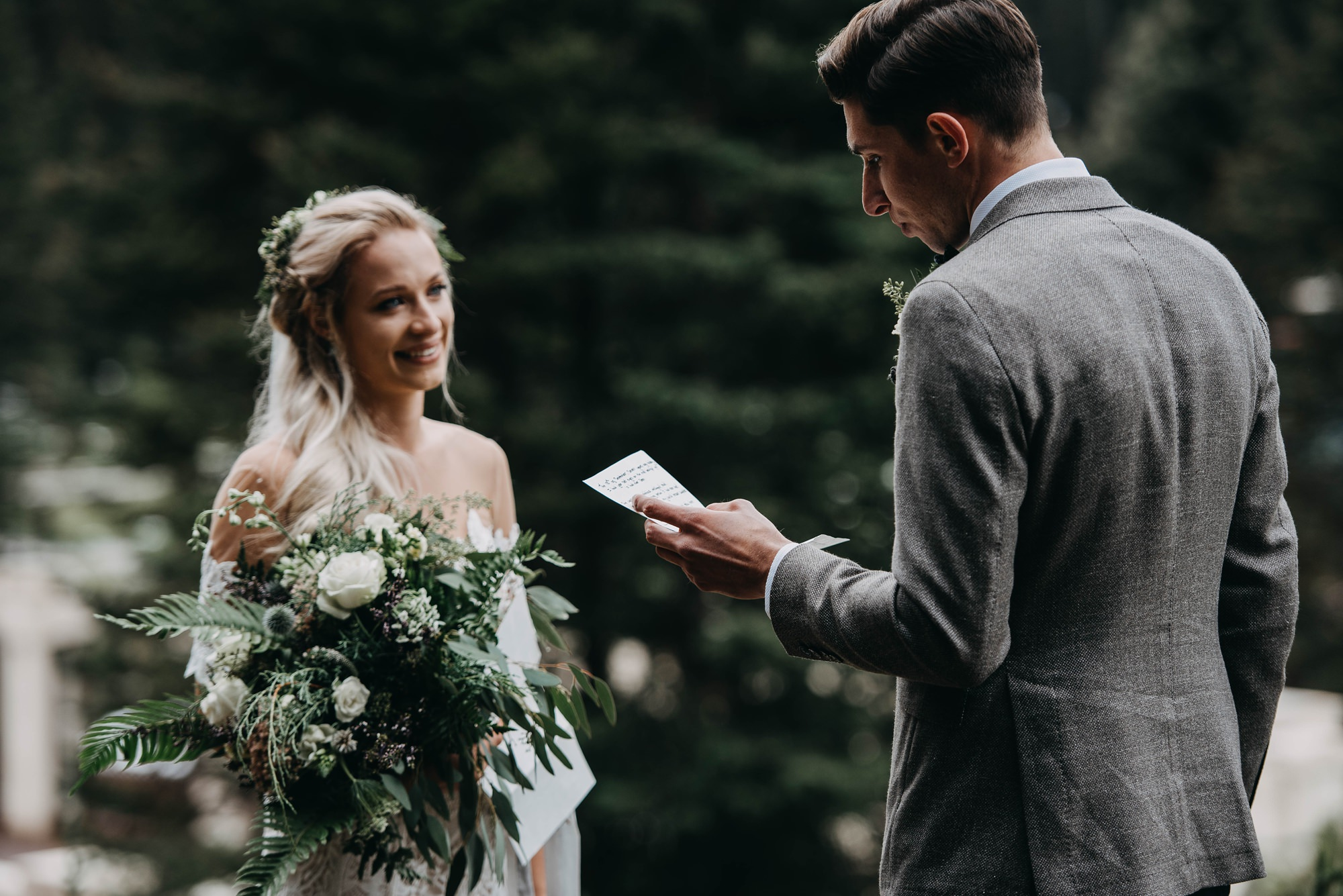 boho intimate wedding captured at Lake Louise, couple reads vows to each other with wild bouquet in moody mountain elopement