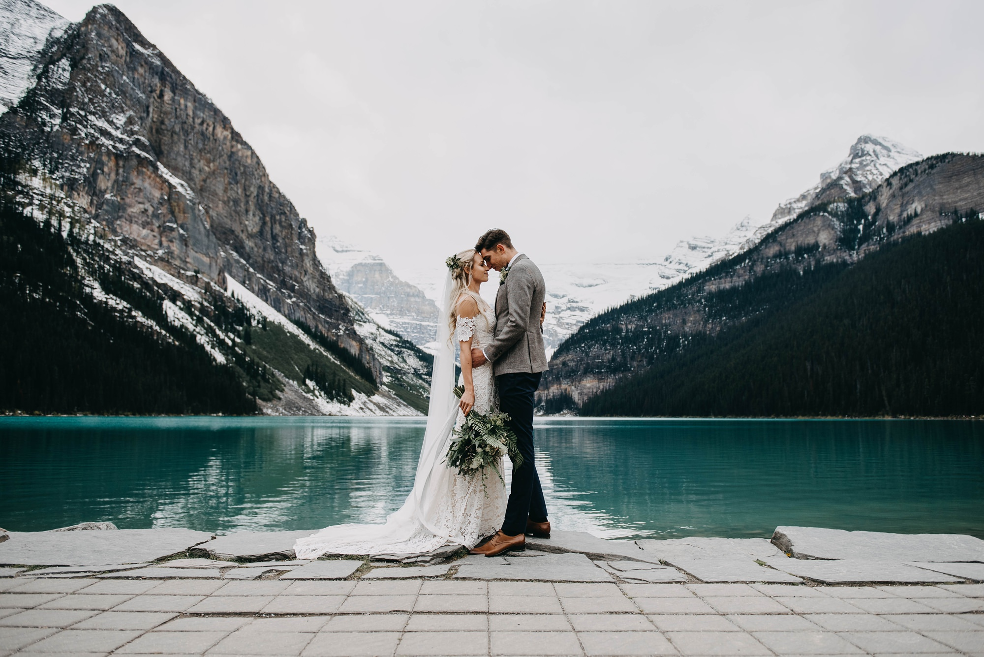stylish boho Bride and groom embracing in front of lake louise