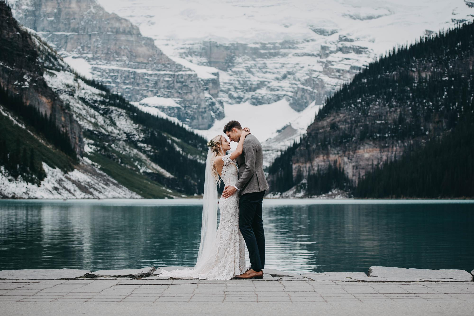 bride and groom at lake louise elopement in snow