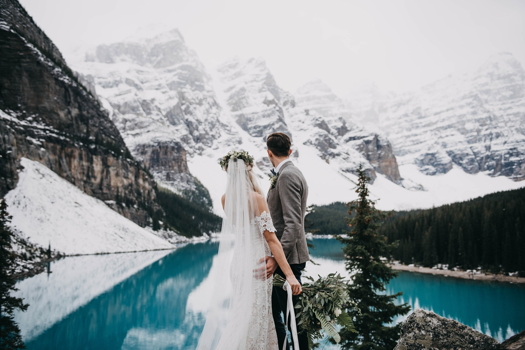 boho bride and stylish groom standing on rock at the cliffside of moraine lake in Lake Louise elopement