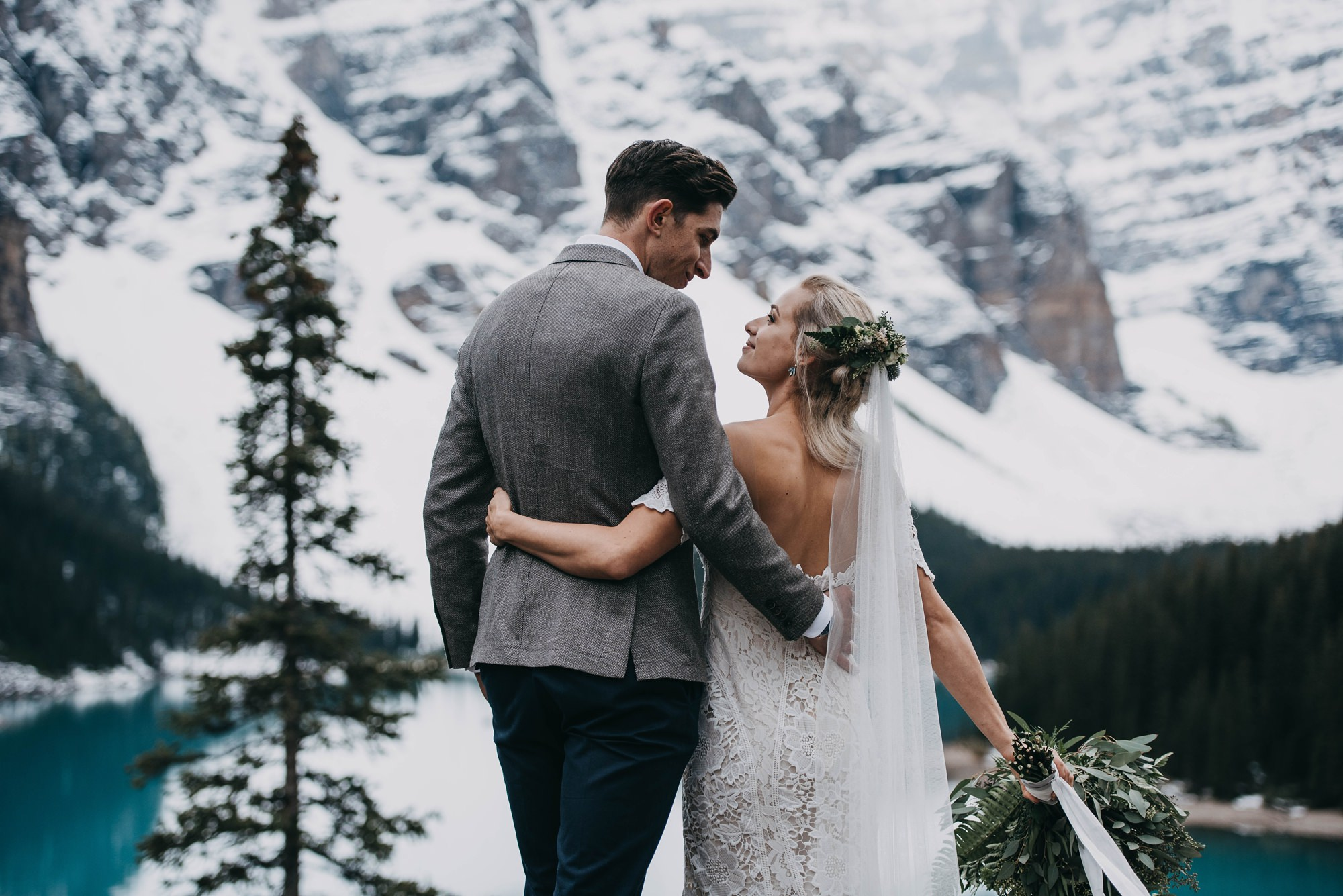 boho bride and stylish groom standing on rock at the cliffside of moraine lake
