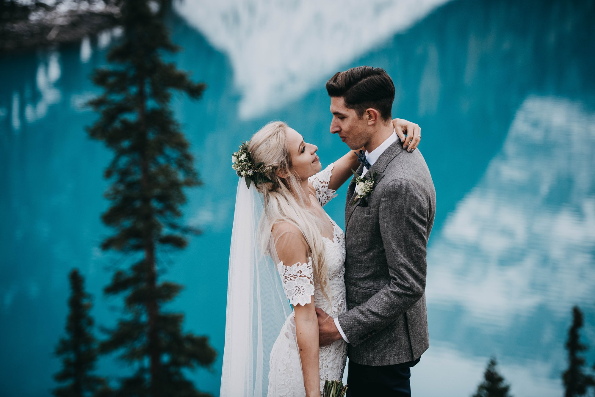 boho bride and stylish groom standing on rock at the cliffside of moraine lake in mountain elopement