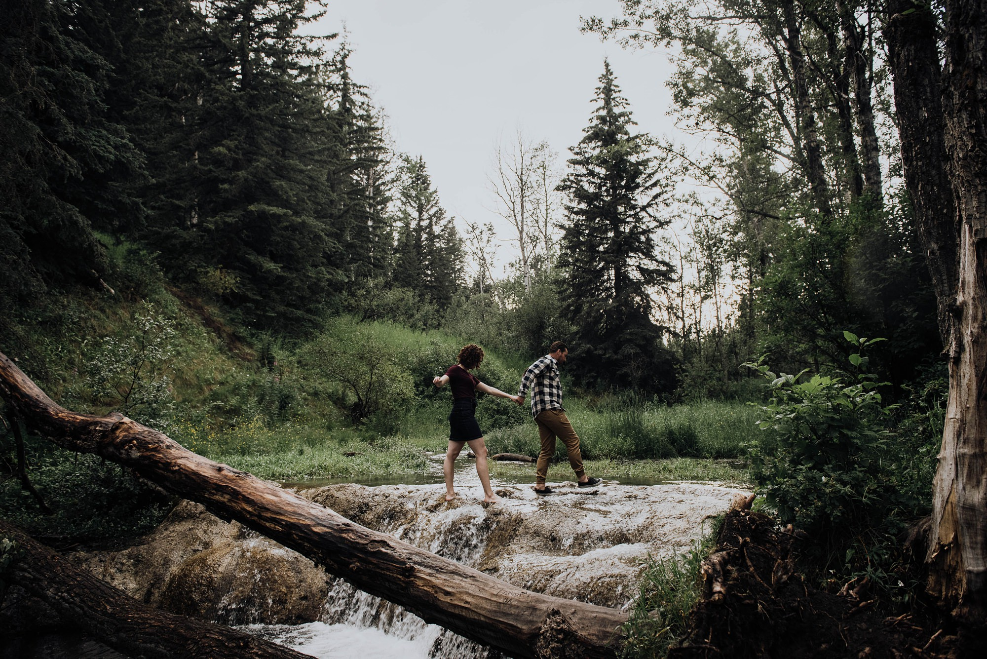 boho stylish couple in love at waterfall in Big Hill Springs Provincial Park engagement session