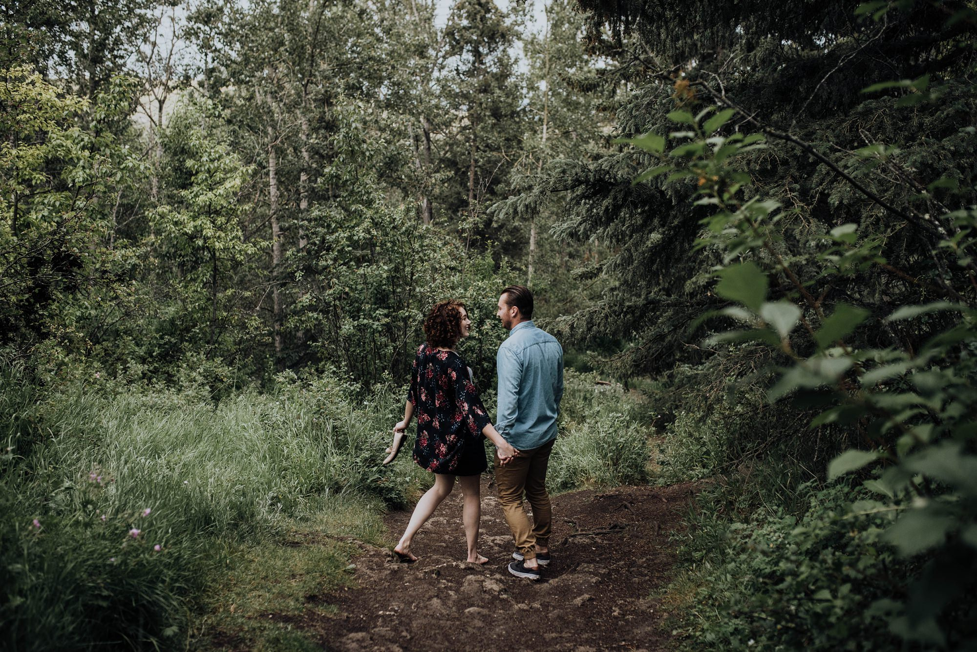 engagement session of stylish couple walking in the forest in big hill springs provincial park alberta