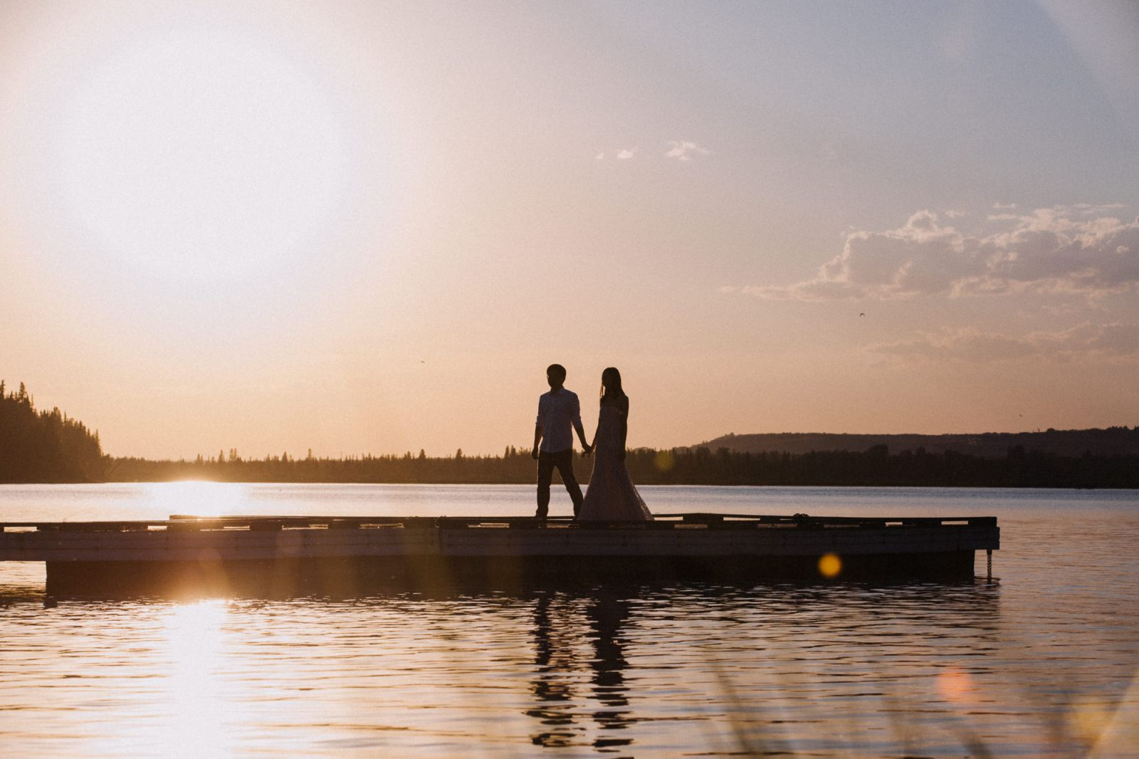 bride and groom walking by the lake with sunset reflection in north glenmore park during heritage park wedding