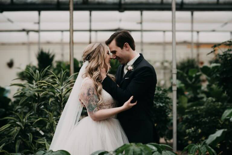 bride and groom kissing during bridal portraits in green house during Calgary winter wedding
