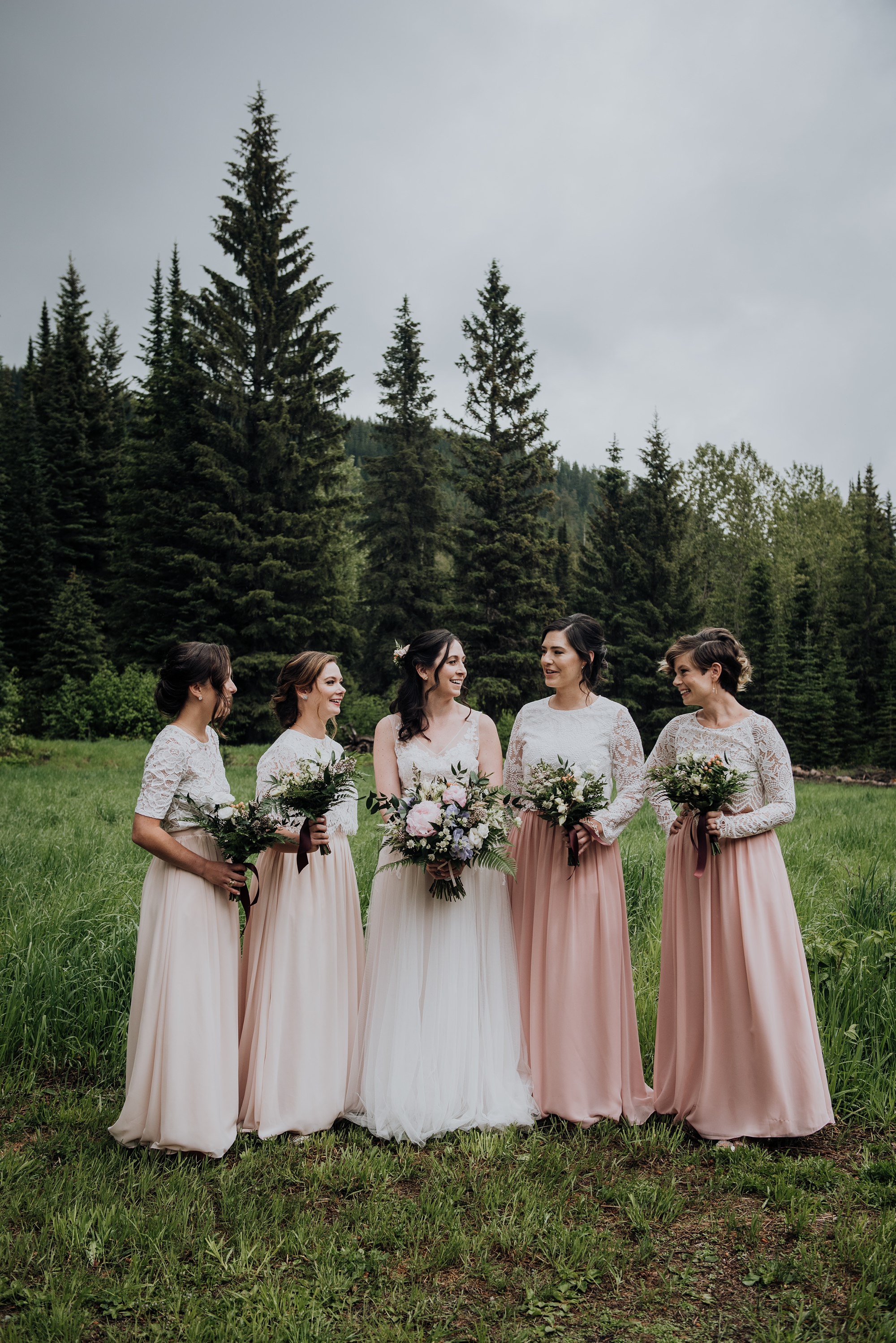 stylish bride and bridesmaids in pink in mountain wedding