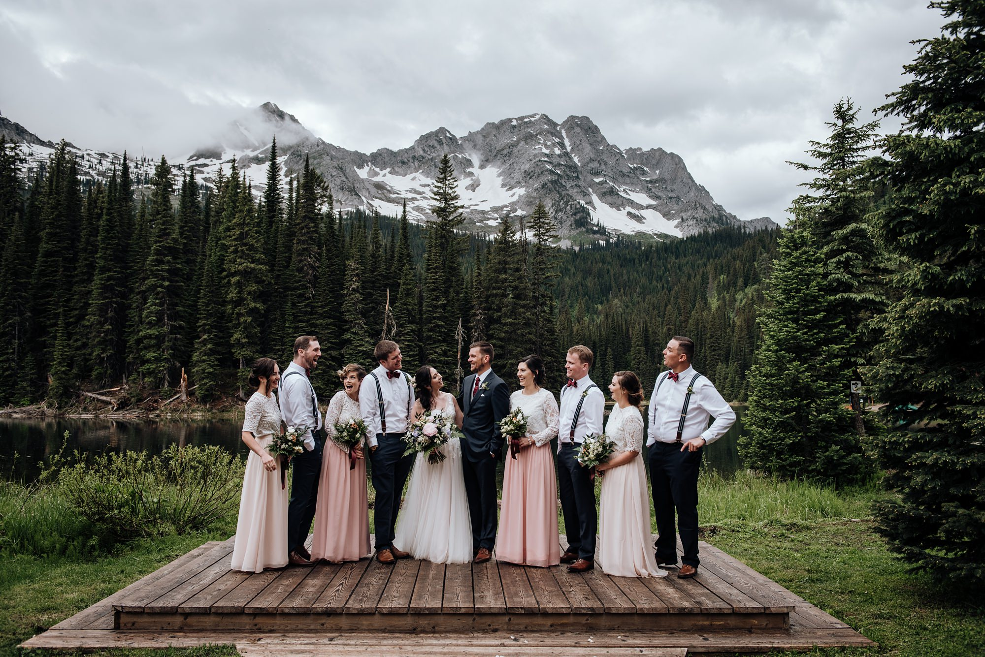 bridal party with bride and groom in front mountains at island lake lodge