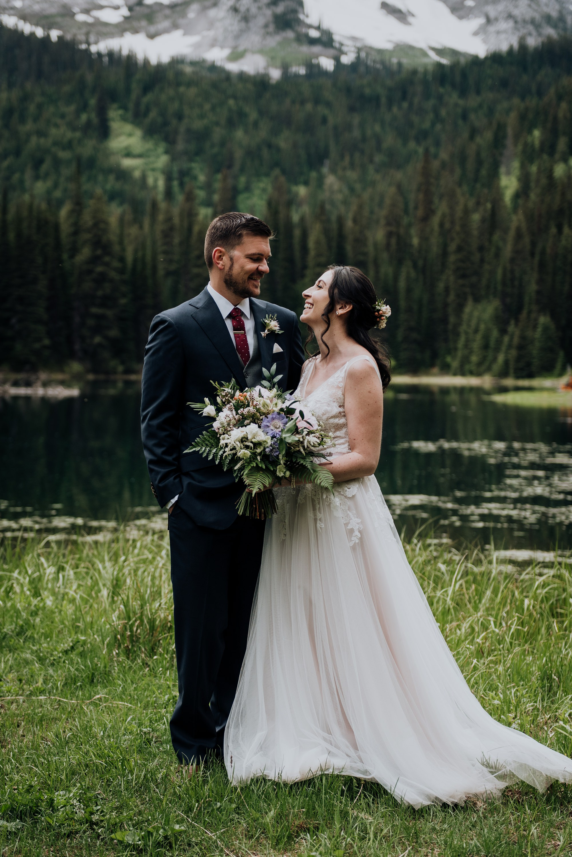 bride and groom in front of lake and mountains at island lake lodge wedding by Calgary wedding photographer