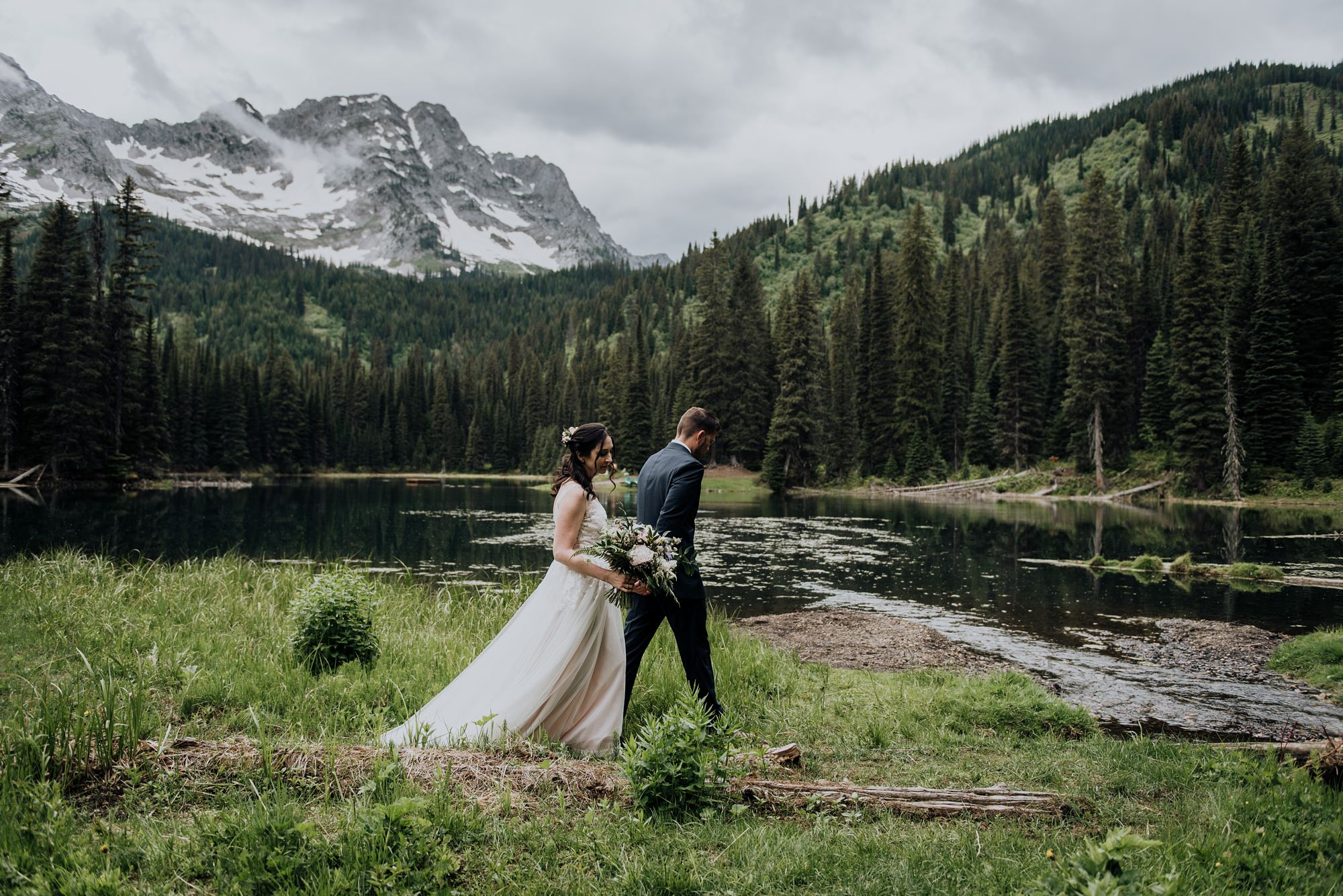 bride and groom in front of lake and mountains at island lake lodge wedding
